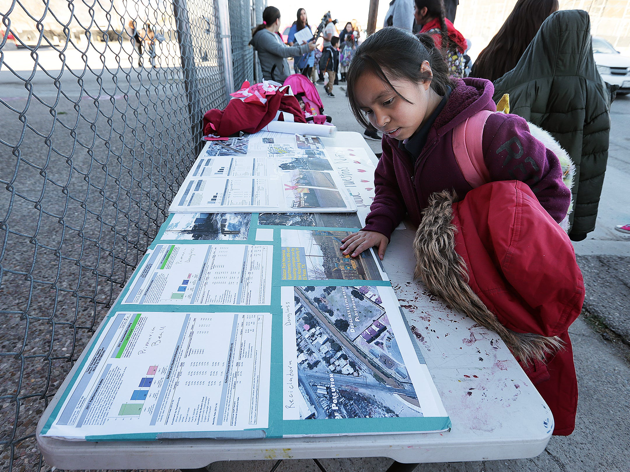 A Beall Elementary School student looks over display boards showing the location of her new school adjacent to a recycling facility. The EPISD Board voted Tuesday to close the school and three others.