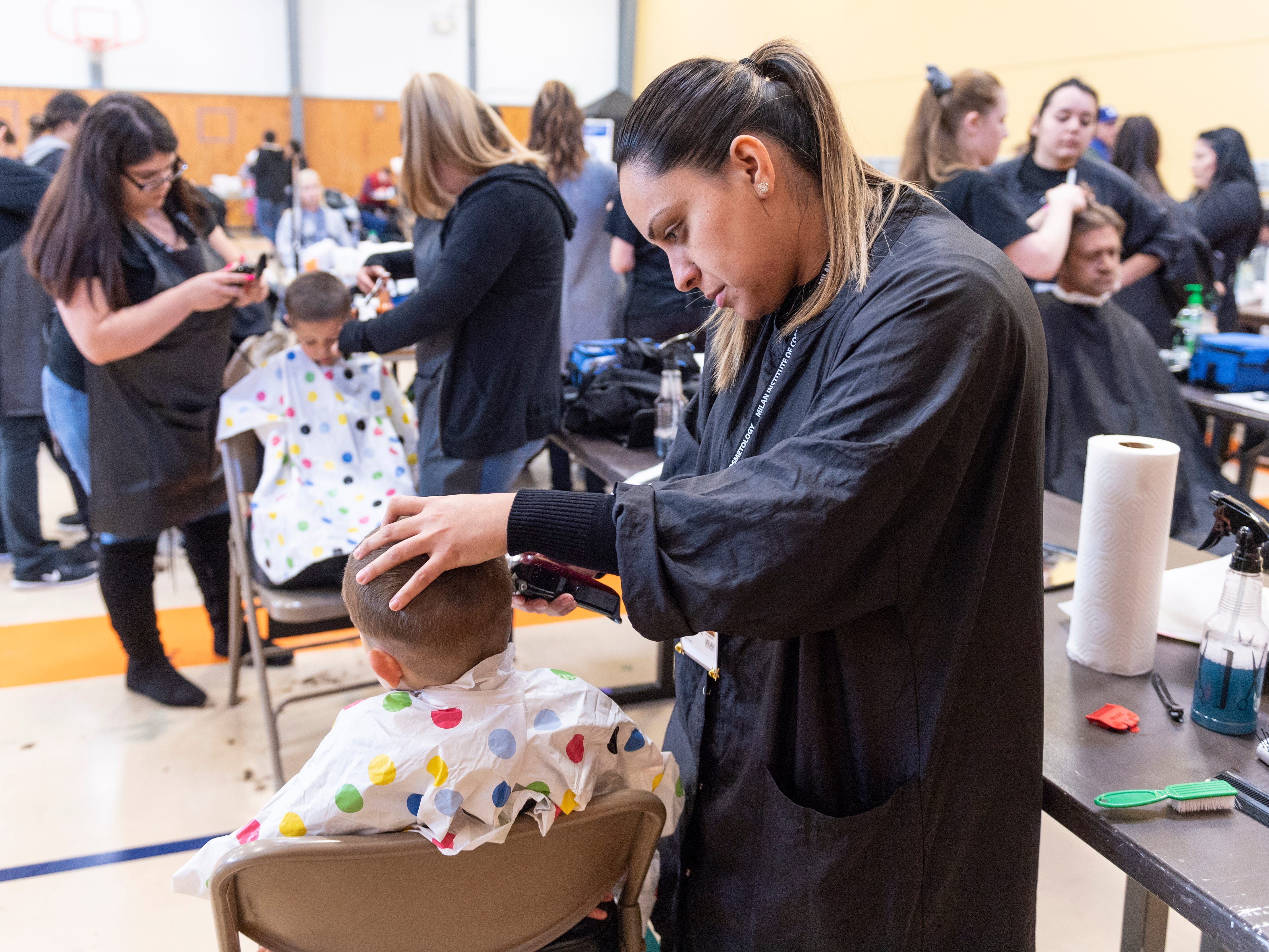 Jesenia Trujillo and other students from Milan cut hair during Project Homeless Connect in Visalia on Thursday, January 24, 2019.