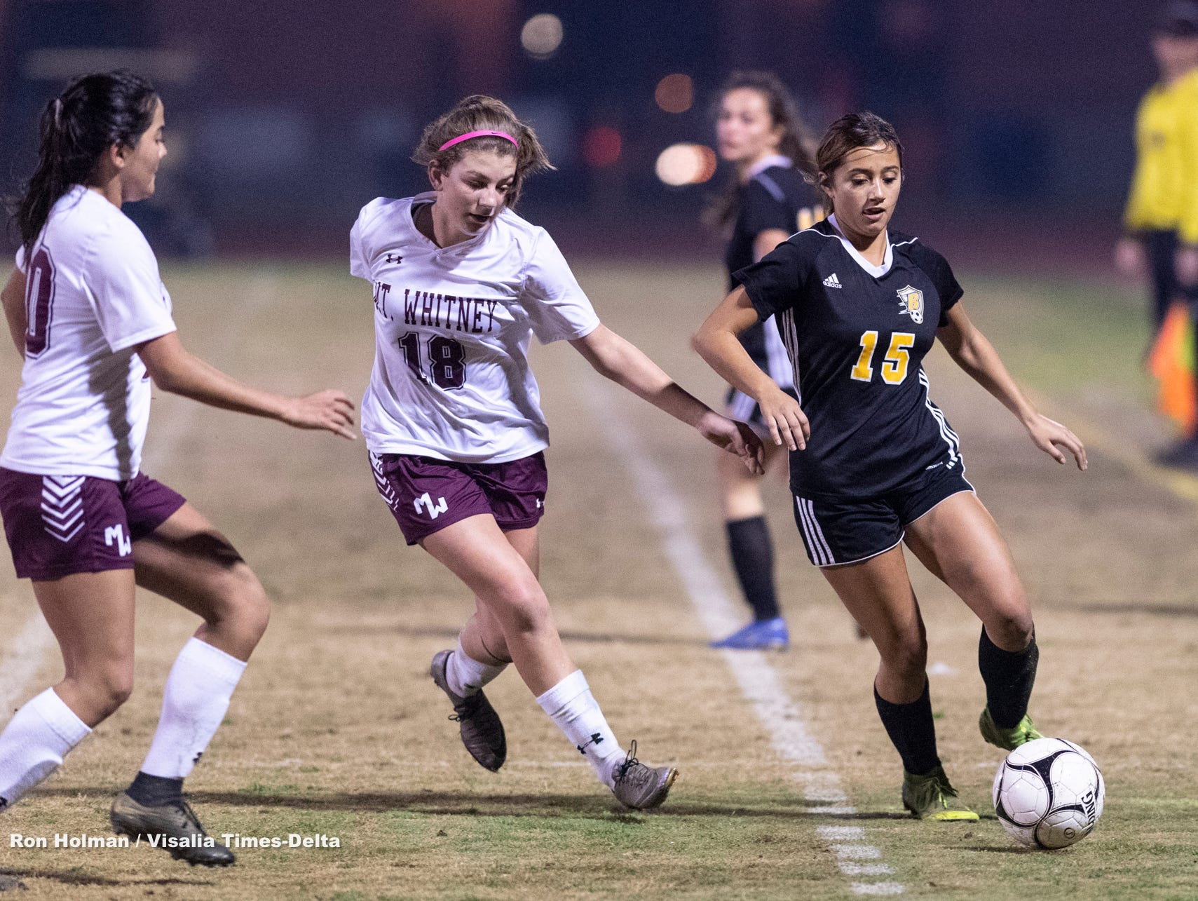 Golden West's Izabel Pelayo, right, gets a pass off ahead of Mt. Whitney's Arianda Villalobos, left, and Brooke Johnson in a girls soccer game on Wednesday, January 23, 2019.