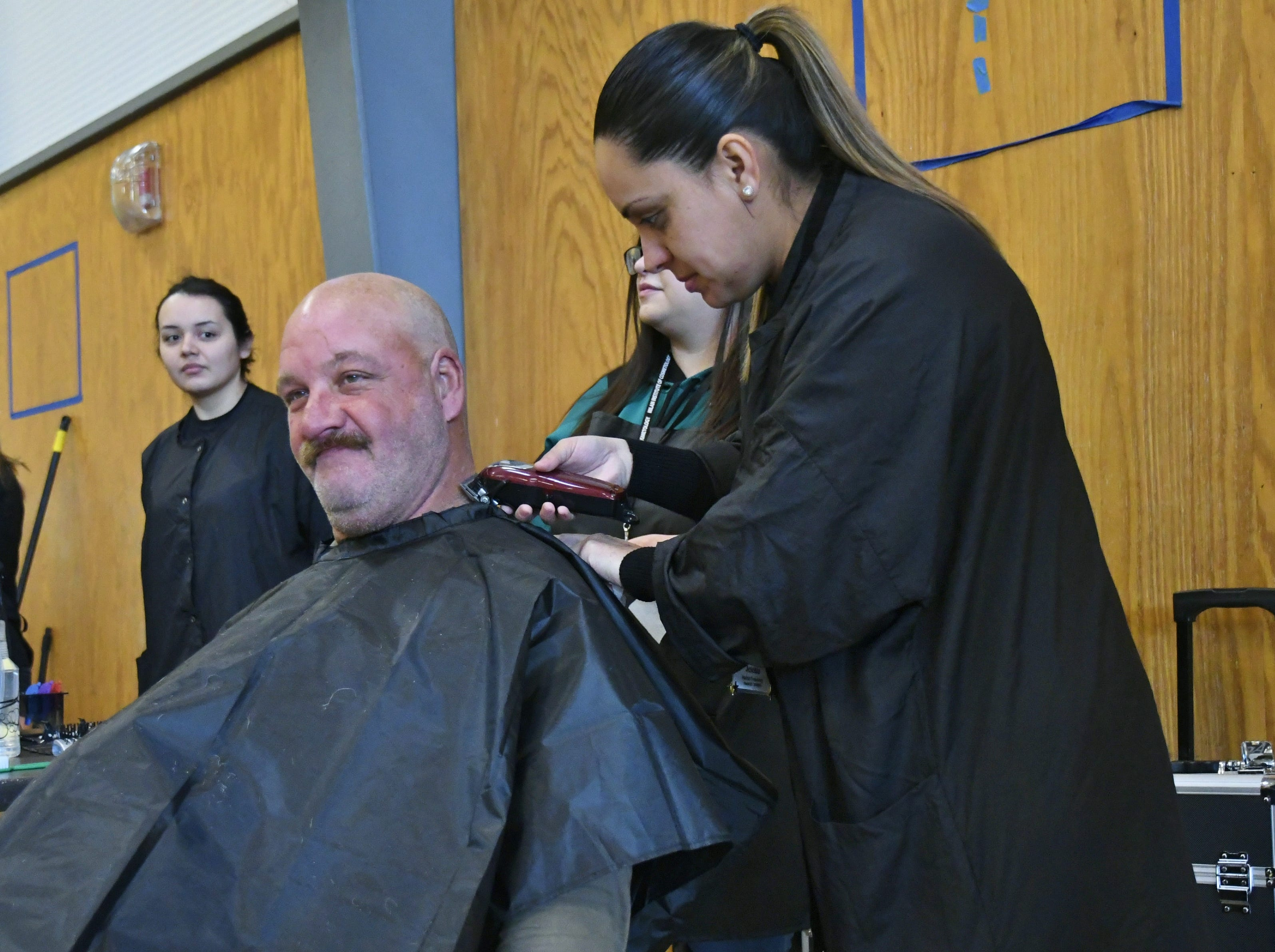 Michael Morgan gets a haircut from Jesenia Trujillo during Project Homeless Connect in Visalia.