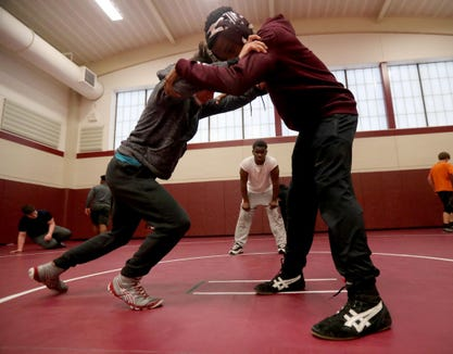Zac Bonner, a senior member of the Ossining High School wrestling team, watches younger wrestlers Tristan Robinson, 13, and Jonathan Benitez, 14, practice Jan. 23, 2019. In December, Bonner was found to have two blood clots in his lungs. Doctors put Bonner on blood thinning medication, making him unable to wrestle. He now acts as an assistant coach on the team, helping out coaches and teammates.