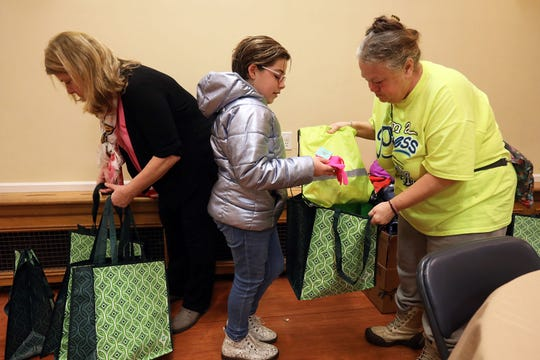 Nyack middle-schooler Josie Rothman, 11, shows a guest what's inside a blessing bag she made with donations Jan. 24, 2019 at Grace Episcopal Church in Nyack. Rothman arrived with 100 bags filled with a scarf, hat, gloves and toiletries for guests at Grace's Kitchen. The church is one of the locations participating in the point-in-time count, a nationwide count of homeless people required by the U.S. Department of Housing and Urban Development (HUD) which sets funding levels based on the count.