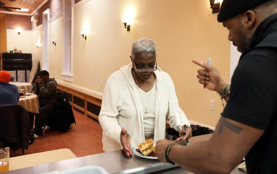 Rev. Owen Thompson hands volunteer Carole Charles of Spring Valley a breakfast at Grace's Kitchen at Grace Episcopal Church in Nyack, Jan. 24, 2019. The church is one of the locations participating in the point-in-time count, a nationwide count of homeless people required by the U.S. Department of Housing and Urban Development (HUD) which sets funding levels based on the count.
