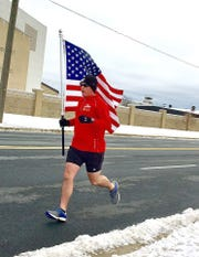 Master Sgt. Trevor Derr, 736th Maintenance Squadron Airframes Powerplant General Section Chief at Dover Air Force Base, carries the American flag during his runs to bring awareness to Post-traumatic stress disorder.