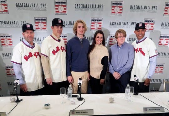 Baseball Hall of Fame inductees Edgar Martinez, left, Mike Mussina, and Mariano Rivera, right, pose for photographs with, Braden Halladay, third from left, Brandy Halladay, center, and Ryan Halladay, after a news conference Wednesday, Jan. 23, 2019, in New York. (AP Photo/Frank Franklin II)