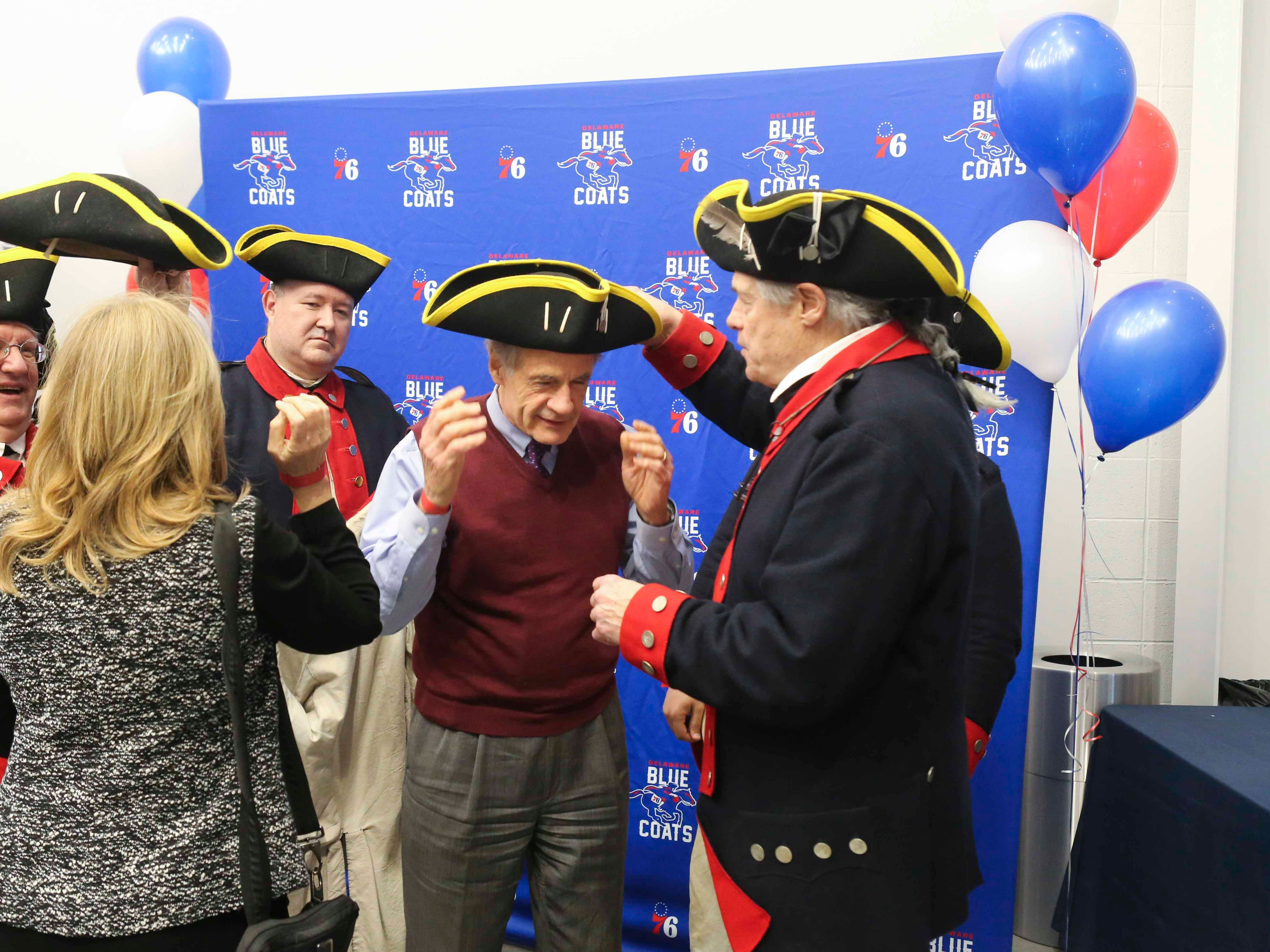 Senator Tom Carper is fitted for a photo with the modern-day version of the namesakes of the Delaware Blue Coats as the NBA G-League team opens the 76ers Field House in Wilmington Wednesday.