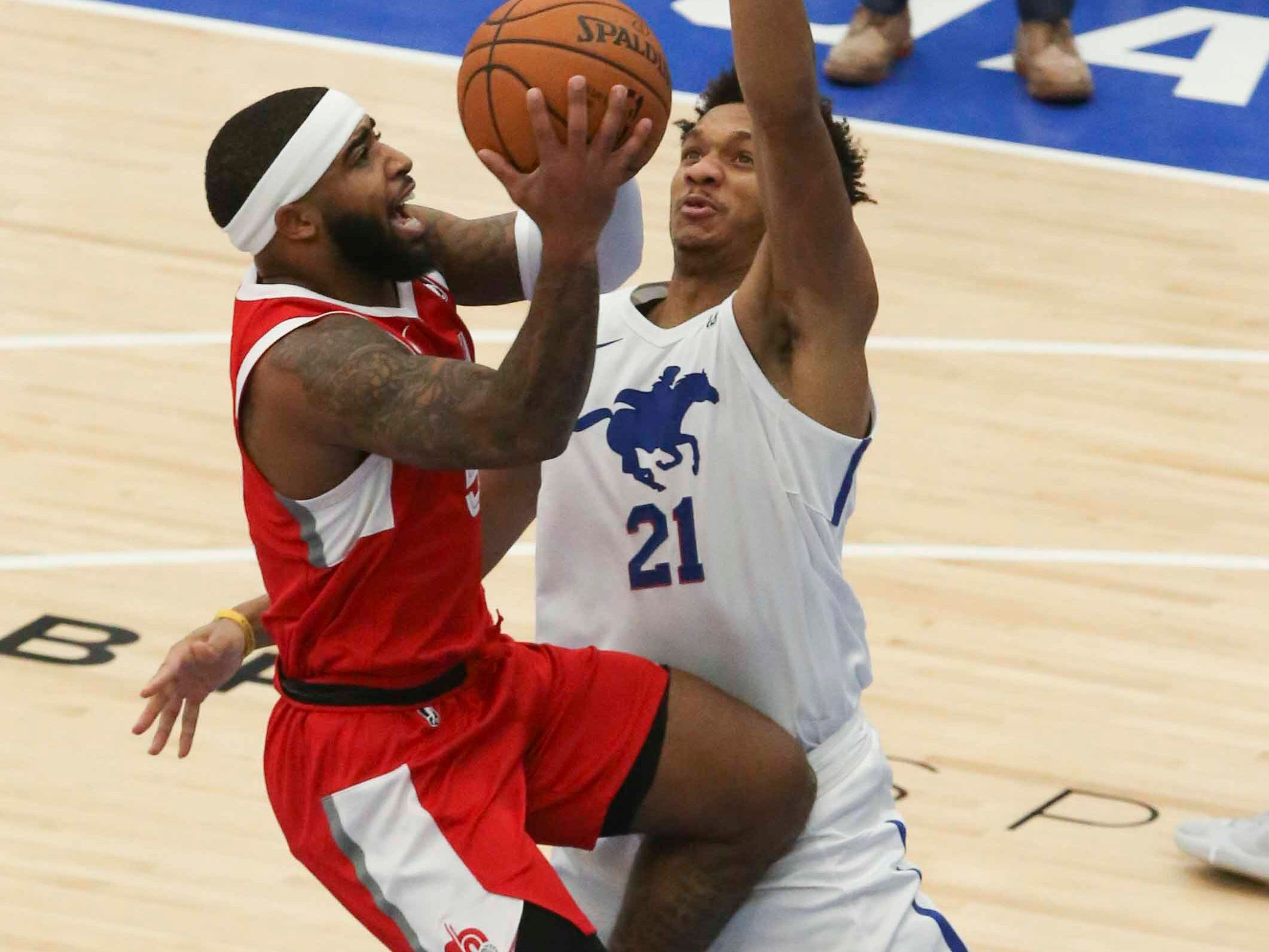 Marcus Keene of the Memphis Hustle (left) drives against the Blue Coats' Rashad Vaughn as the Delaware Blue Coats of the NBA G-League open the 76ers Field House in Wilmington Wednesday.
