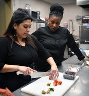 Courtney Ragsdale, left, and Tamitha Bailey of Southern Girl Cafe & Catering at the Wichita Falls Regional Airport, talk while doing prep work in the kitchen. The cafe is serving free hamburgers Friday from 11:00 a.m. to 1:00 p.m. to furloughed federal employees.