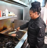 Tamitha Bailey, owner of Southern Girl Cafe & Catering, cooks a hamburger at the restaurant in the Wichita Falls Regional Airport. The cafe will serve free hamburgers to furloughed federal employees Friday from 11:00 a.m. to 1:00 p.m.