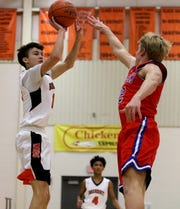 Burkburnett's Andrew Hawkins shoots from three-point range over Graham's Daniel Gilbertson Tuesday, Jan. 22, 2019, in Burkburnett. The Bulldogs defeated the Steers 83-68.
