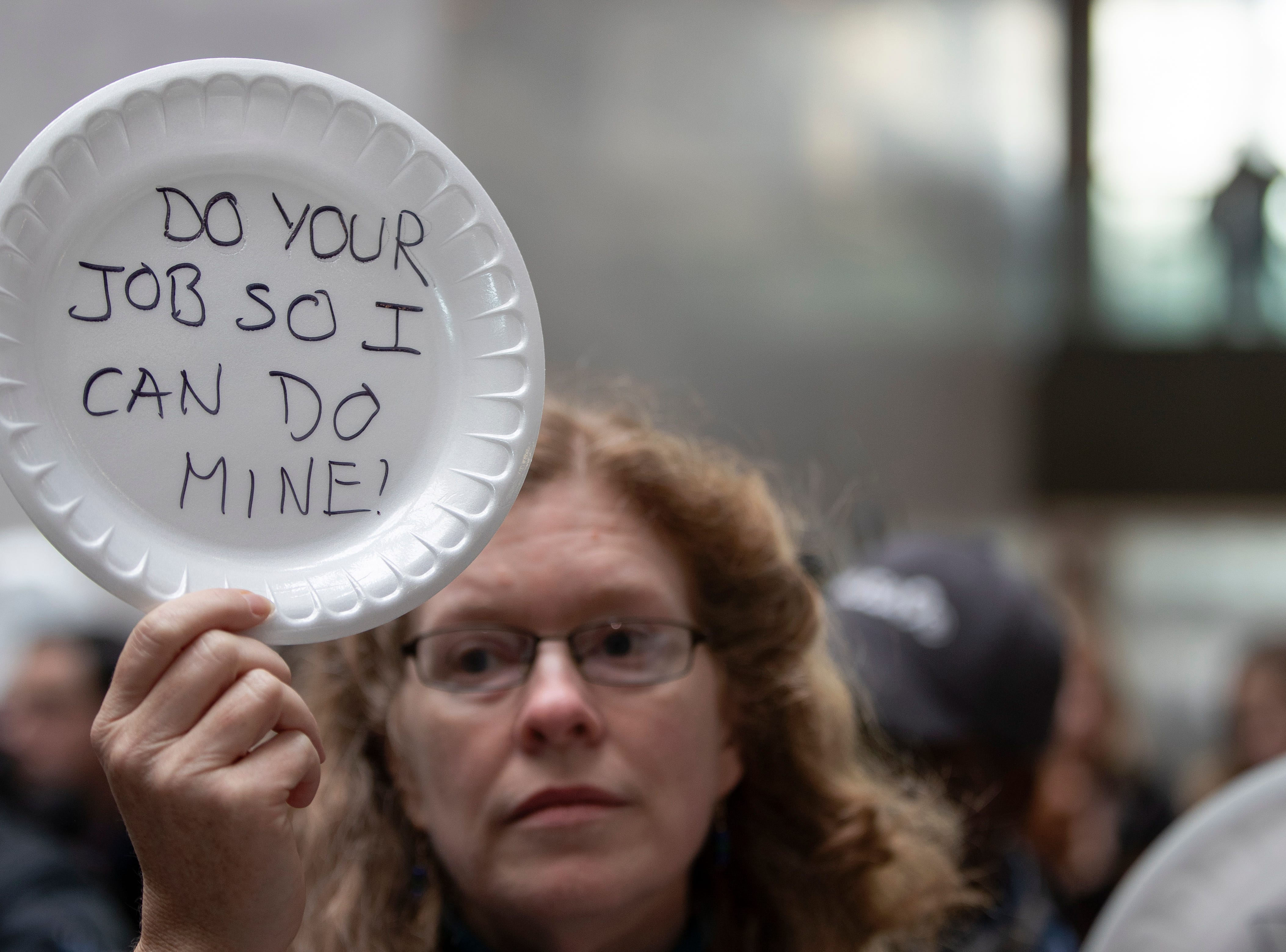 A woman displays her thoughts, written out on a disposable plate, during the 'Occupy Hart' protest against the partial government shutdown sponsored by American Federation of Government Employees at the Hart Senate Office Building at the US Capitol in Washington, DC on 23 Jan. 23, 2019. Federal workers and their supporters stood silently for 33 minutes for the 33 days of the shutdown.