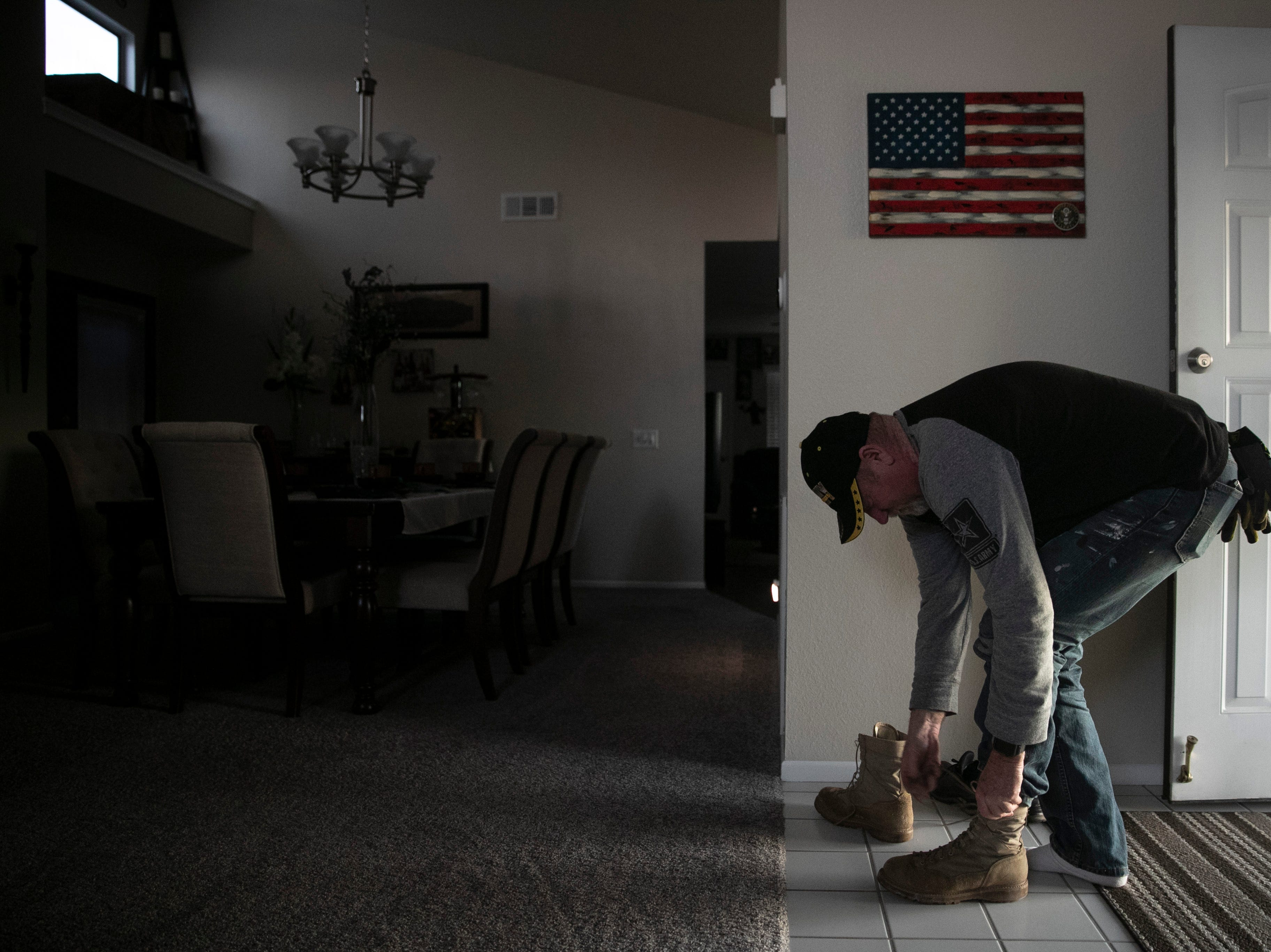 "Chris George, a federal employee furloughed from his job as a forestry technician supervisor for the U.S. Department of Agriculture Forest Service, takes off his boots at his home adorned with an American flag after spending the day working as a handyman Saturday, Jan. 19, 2019, in Hemet, Calif. ""I have a lot of pride, so asking for help is difficult for me. It's very difficult for me because I'm always the one giving back or putting myself before anybody else,"" said George. ""Now, here I am in the situation where I'm the one that is in need."""
