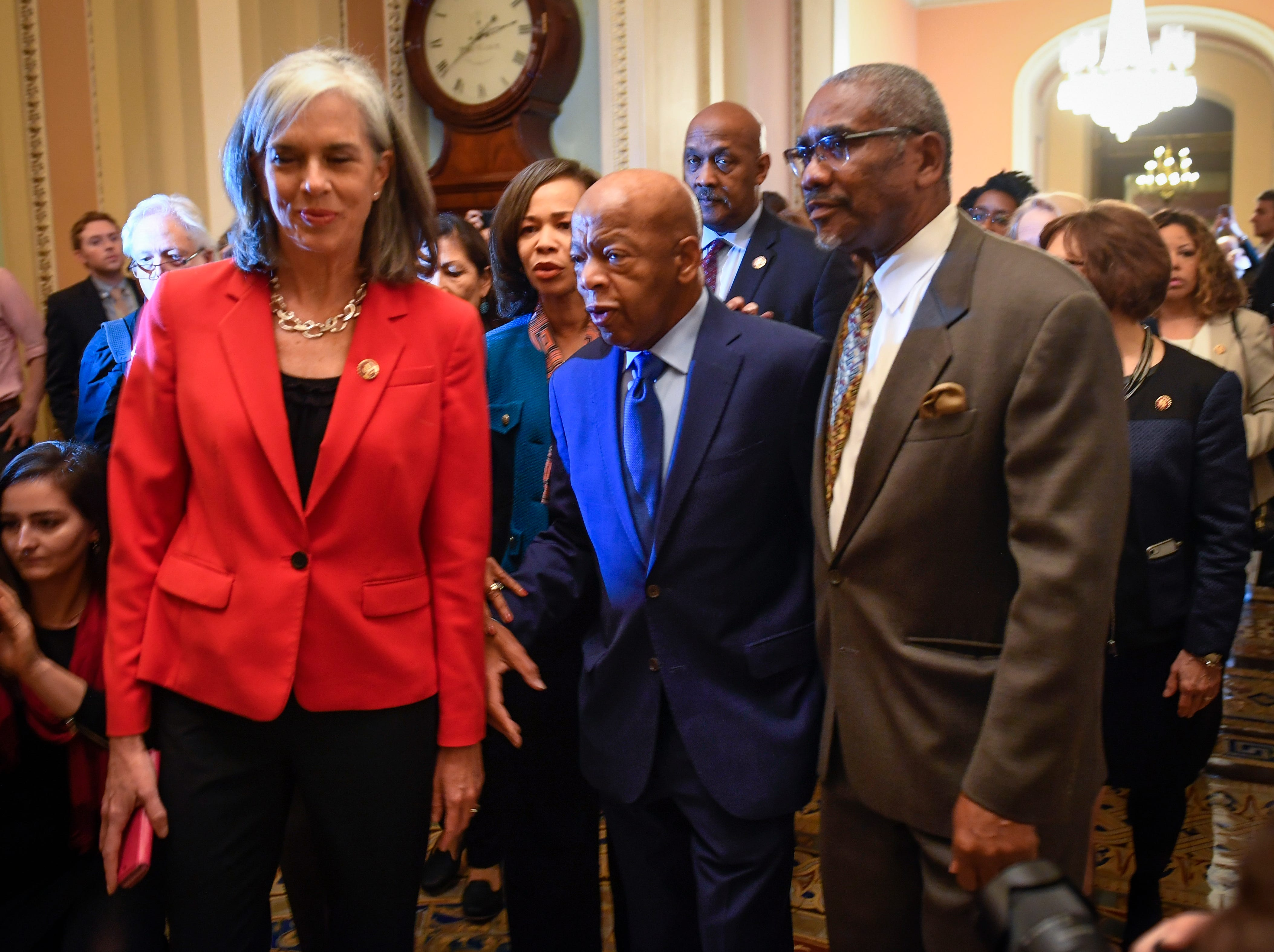 Rep. John Lewis (D-GA), center, and other Democratic House members walk into the Senate chambers before the Senate rejected a pair of dueling bills Thursday.