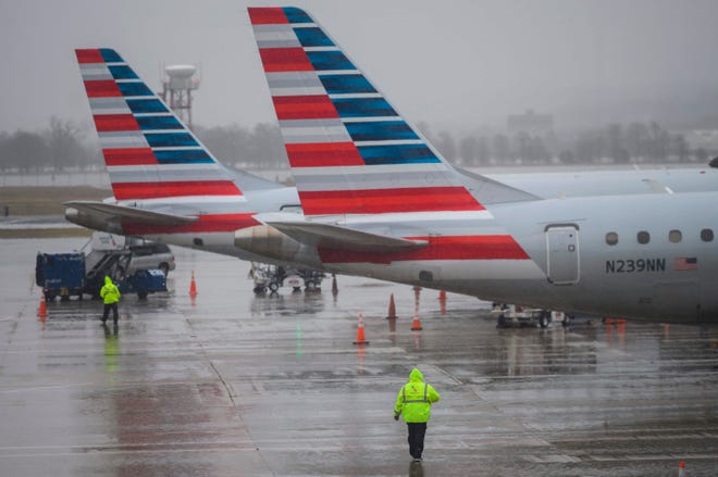 An American Airlines ground staff member walks towards planes on the tarmac at Ronald Reagan Washington National Airport in Arlington, Virginia on Jan. 24, 2019.  American Airlines executives warned of significant travel delays if the US government shutdown goes on much longer, but said that customer demand has not been significantly affected thus far.