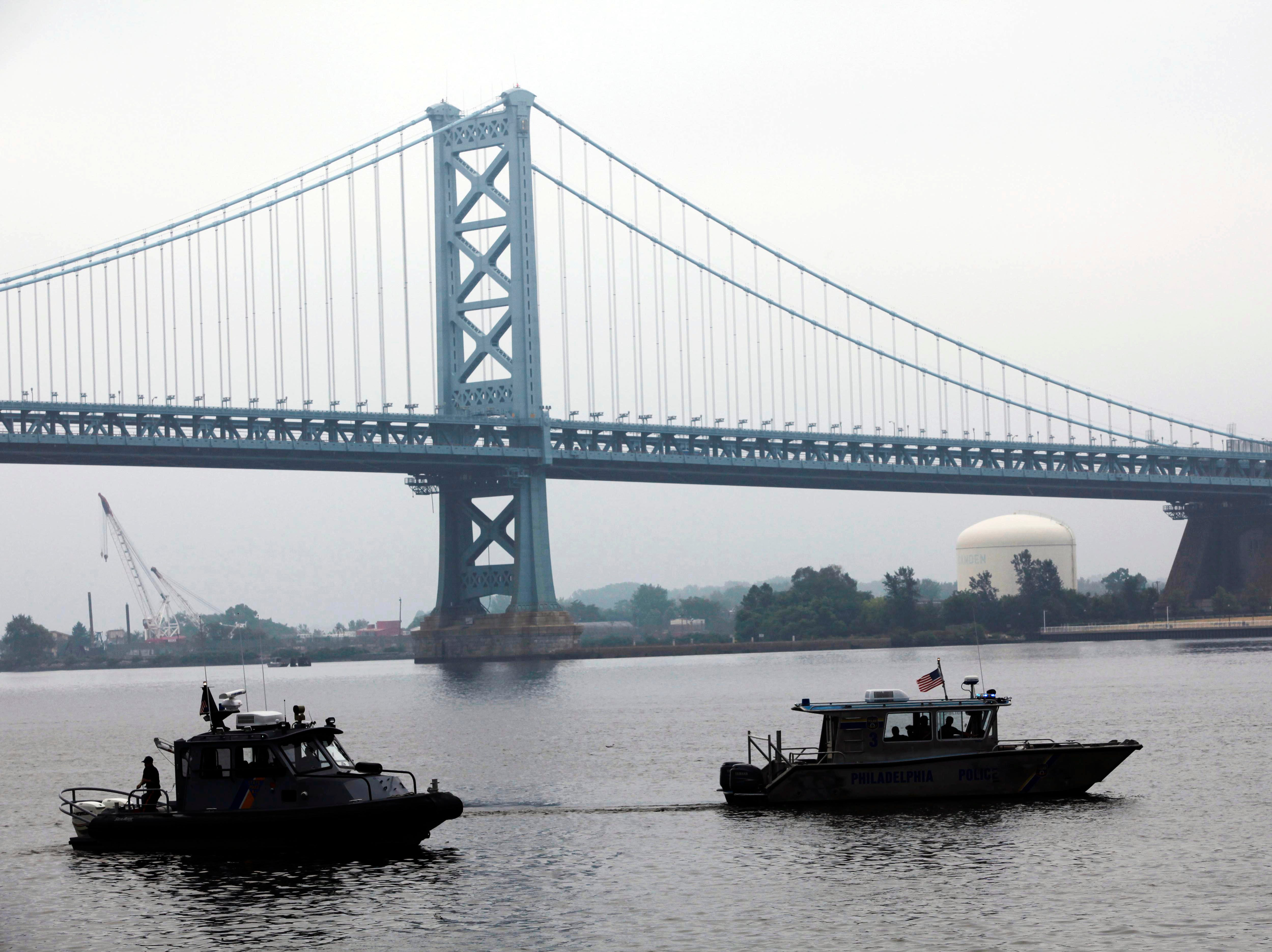 ORG XMIT: PAMR102 Search vessels look for two missing tour boat passengers on the Delaware River in view of the Benjamin Franklin Bridge in Philadelphia, Thursday, July 8, 2010. The passengers' amphibious craft in which they were riding was struck and sunk by a barge Wednesday. (AP Photo/Matt Rourke)