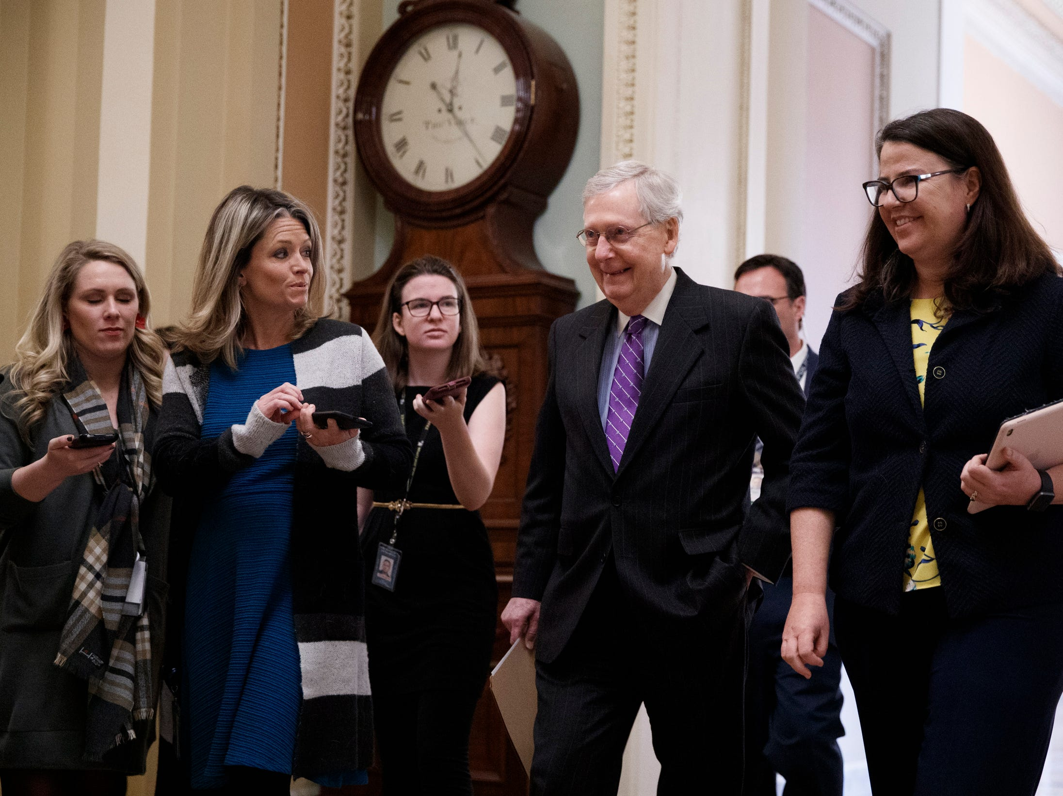 Senate Majority Leader Mitch McConnell (2-L) walks from his office to the Senate floor to deliver remarks in the US Capitol Capitol, Wednesday. The partial US government shutdown continues into its 33rd day as competing bills are being considered in the Senate.