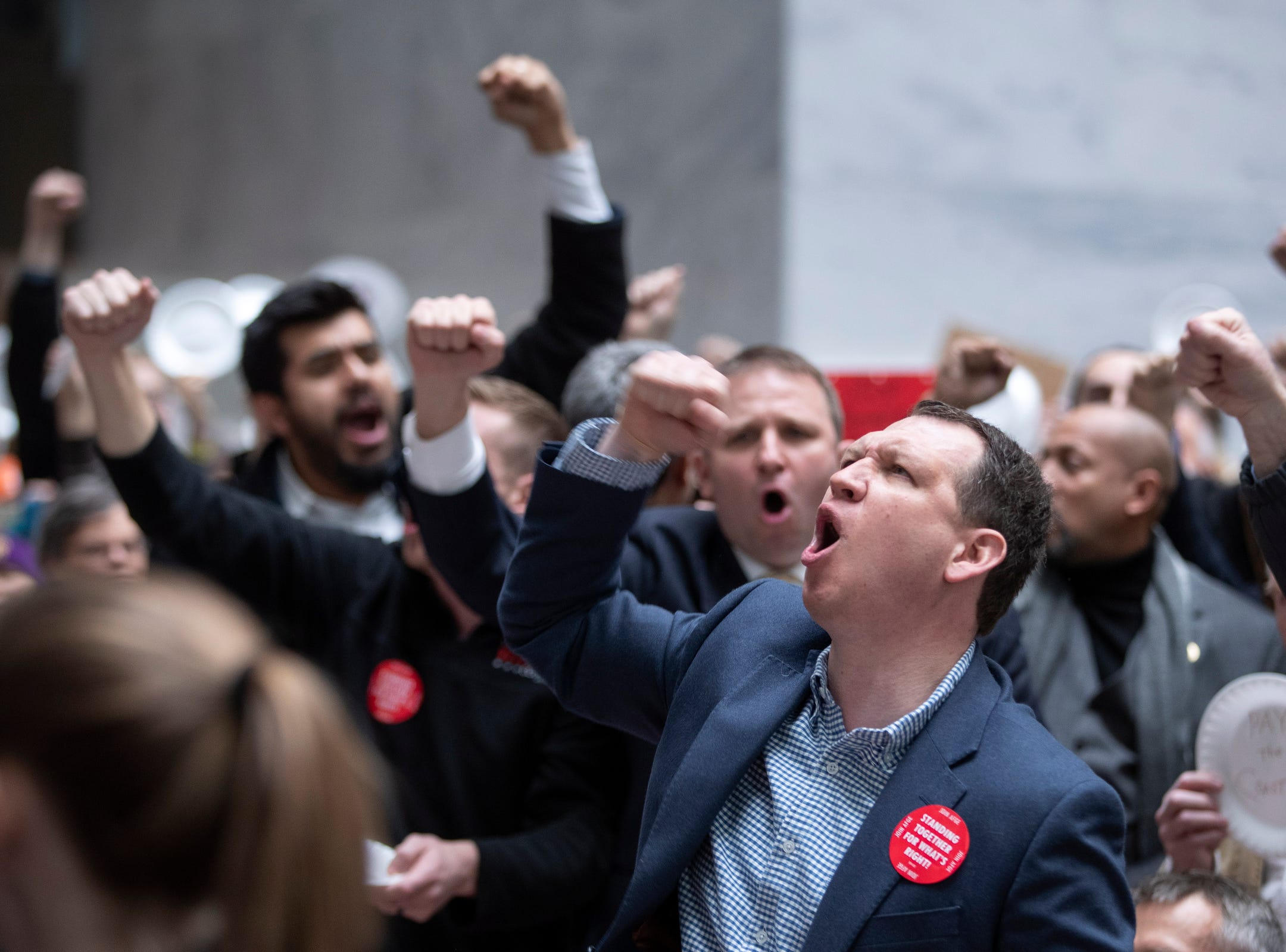 People shout slogans as they participate in the 'Occupy Hart' protest against the partial government shutdown sponsored by American Federation of Government Employees at the Hart Senate Office Building in Washington, DC.