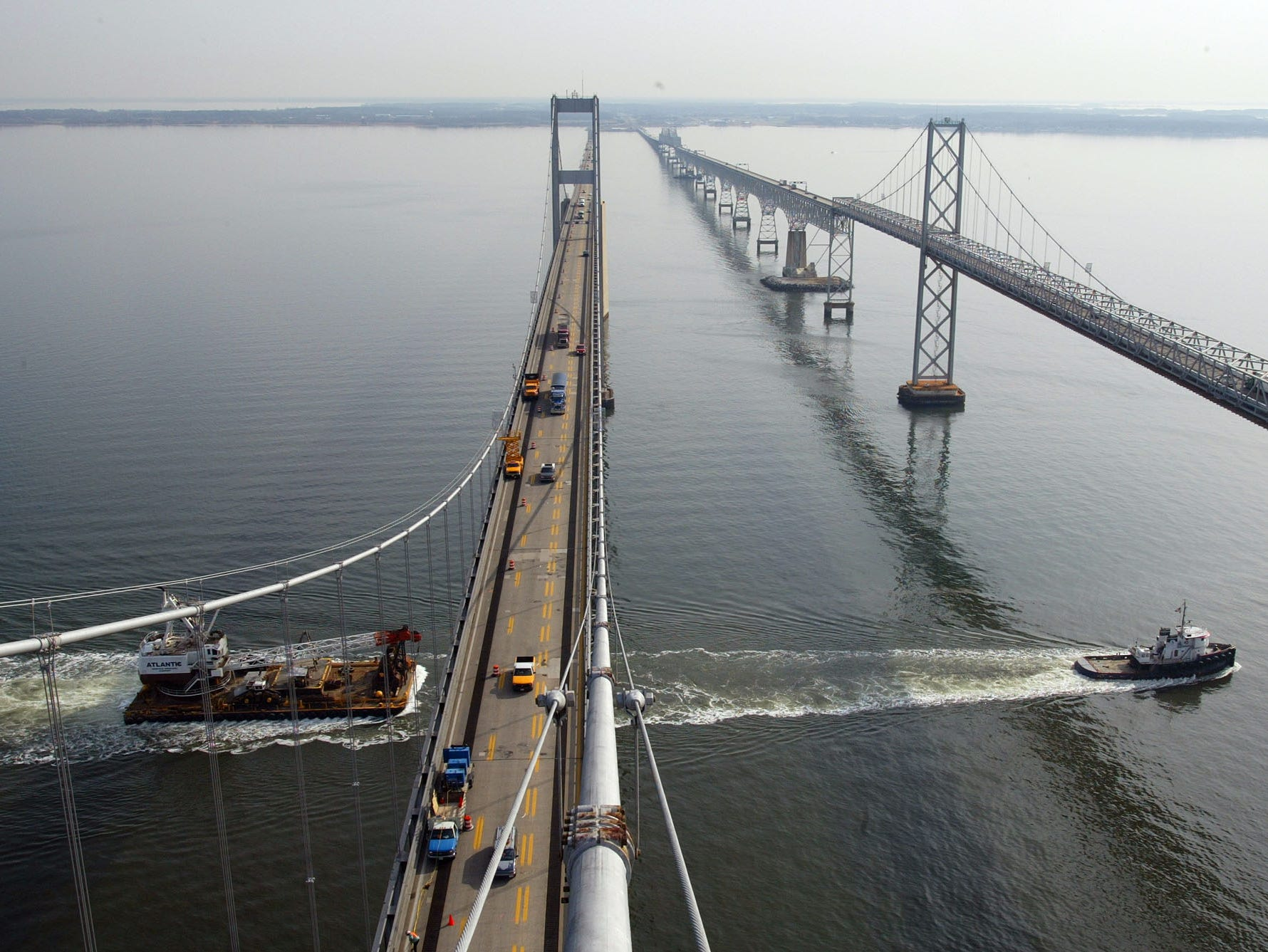 ** FILE ** In this view, looking east from a tower of the westbound span of the Chesapeake Bay Bridge, a tugboat tows a barge south on the Chesapeake Bay on Jan. 30, 2002.   When it first opened to traffic on July 30, 1952, what's popularly known today as the Chesapeake Bay Bridge was the third-longest in the world. In 50 years, the architectural marvel accelerated trade, opened new markets to farmers and brought Ocean City beaches hours closer to tourists, single-handedly changing the complexion of commerce in Maryland.  The eastbound span of the bridge, right, was completed in 1952, while the westbound span was completed in 1973. (AP Photo/Roberto Borea) ORG XMIT: BA106