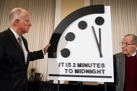 Former California Gov. Jerry Brown, left, and former Secretary of Defense William Perry unveil the Doomsday Clock during the Bulletin of the Atomic Scientists news conference in Washington, Thursday, Jan. 24, 2019.  The Doomsday Clock is set at two minutes to midnight.