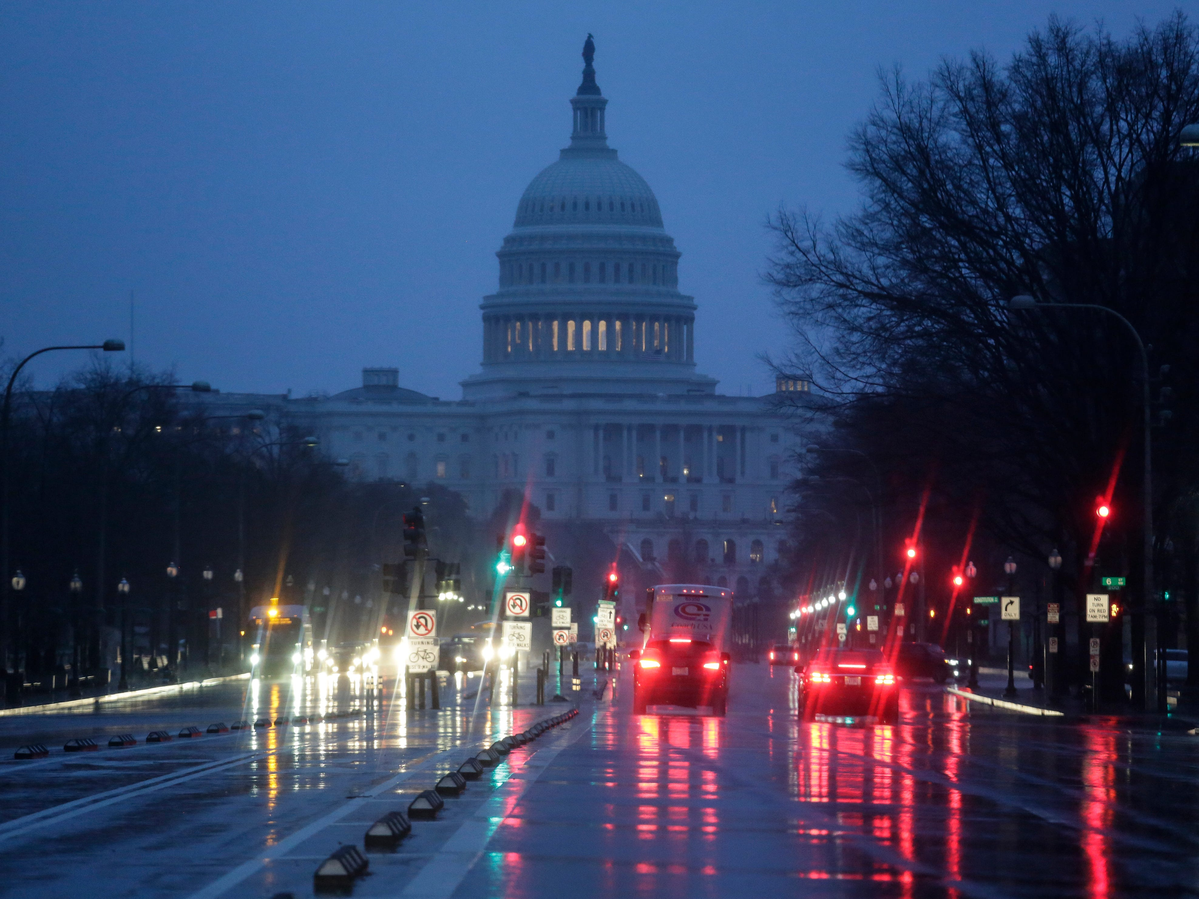 The Capitol is seen early Thursday, Jan. 24, 2019, as rain falls on Pennsylvania Avenue in Washington, with the partial government shutdown in its second month. The Senate will vote on two competing proposals today to end the impasse, but neither seems to have enough votes to advance.
