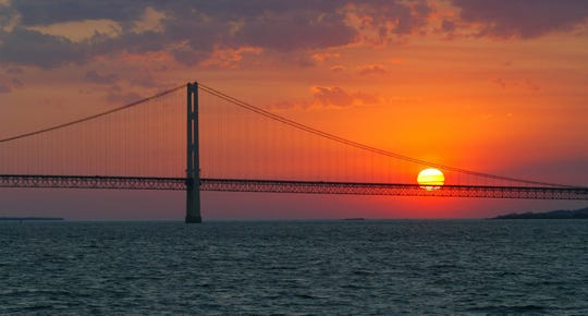 FILE - In this May 31, 2002 file photo, the sun sets over the Mackinac Bridge and the Mackinac Straits as seen from Lake Huron. The bridge is the dividing line between Lake Michigan to the west and Lake Huron to the east. President Donald Trump again is trying to drastically reduce or eliminate federal support for cleanups of some iconic U.S. waterways. His proposed budget would slash Environmental Protection Agency funding for Great Lakes and Chesapeake Bay restoration programs by 90 percent. It would kills all EPA spending on programs supporting other waters including San Francisco Bay, the Gulf of Mexico and Puget Sound. The administration made a similar attempt last year but Congress refused to go along. (AP Photo/Al Goldis, File) ORG XMIT: CER204