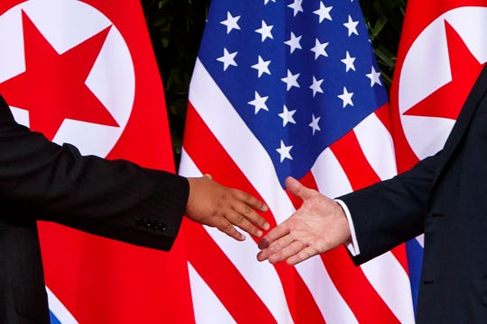 In this Tuesday, June 12, 2018, file photo, U.S. President Donald Trump, right, reaches to shake hands with North Korea leader Kim Jong Un at the Capella resort on Sentosa Island in Singapore.