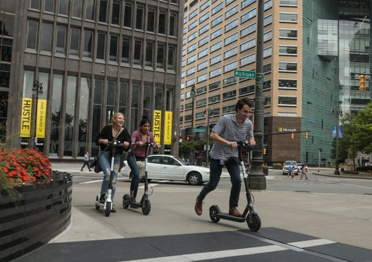 Alexis Richards of Detroit, left, Jasmine Tisnado of Las Vegas and Julian Weinberg of Detroit take off while riding rented Bird electric scooters in downtown Detroit.