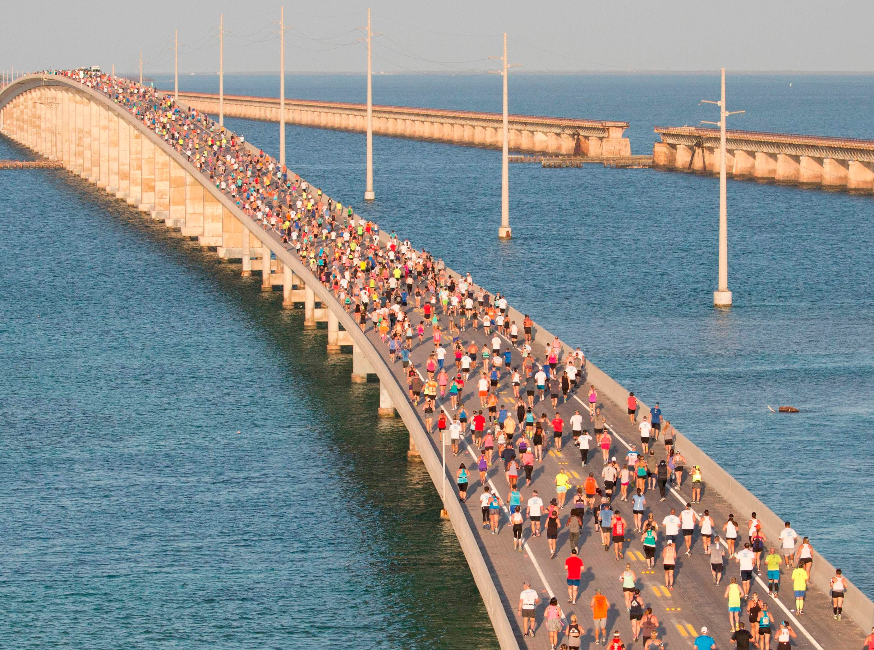 """In this aerial photo provided by the Florida Keys News Bureau, a portion of a field of about 1,500 runners reaches the top of the Florida Keys Overseas Highway's longest bridge during the Seven Mile Bridge Run Saturday, April 14, 2018, near Marathon, Florida.  The race over the convergence of the Atlantic Ocean and Gulf of Mexico was initiated in 1982 to mark the completion of a federally funded bridge rebuilding program to replace 37 aging spans originally built in the early 1900s to carry railroad trains.  / AFP PHOTO / Florida Keys News Bureau / Bob Care / RESTRICTED TO EDITORIAL USE - MANDATORY CREDIT """"AFP PHOTO / Florida Keys News Bureau / Bob CARE"""" - NO MARKETING NO ADVERTISING CAMPAIGNS - DISTRIBUTED AS A SERVICE TO CLIENTS  BOB CARE/AFP/Getty Images ORIG FILE ID: AFP_14133P"""