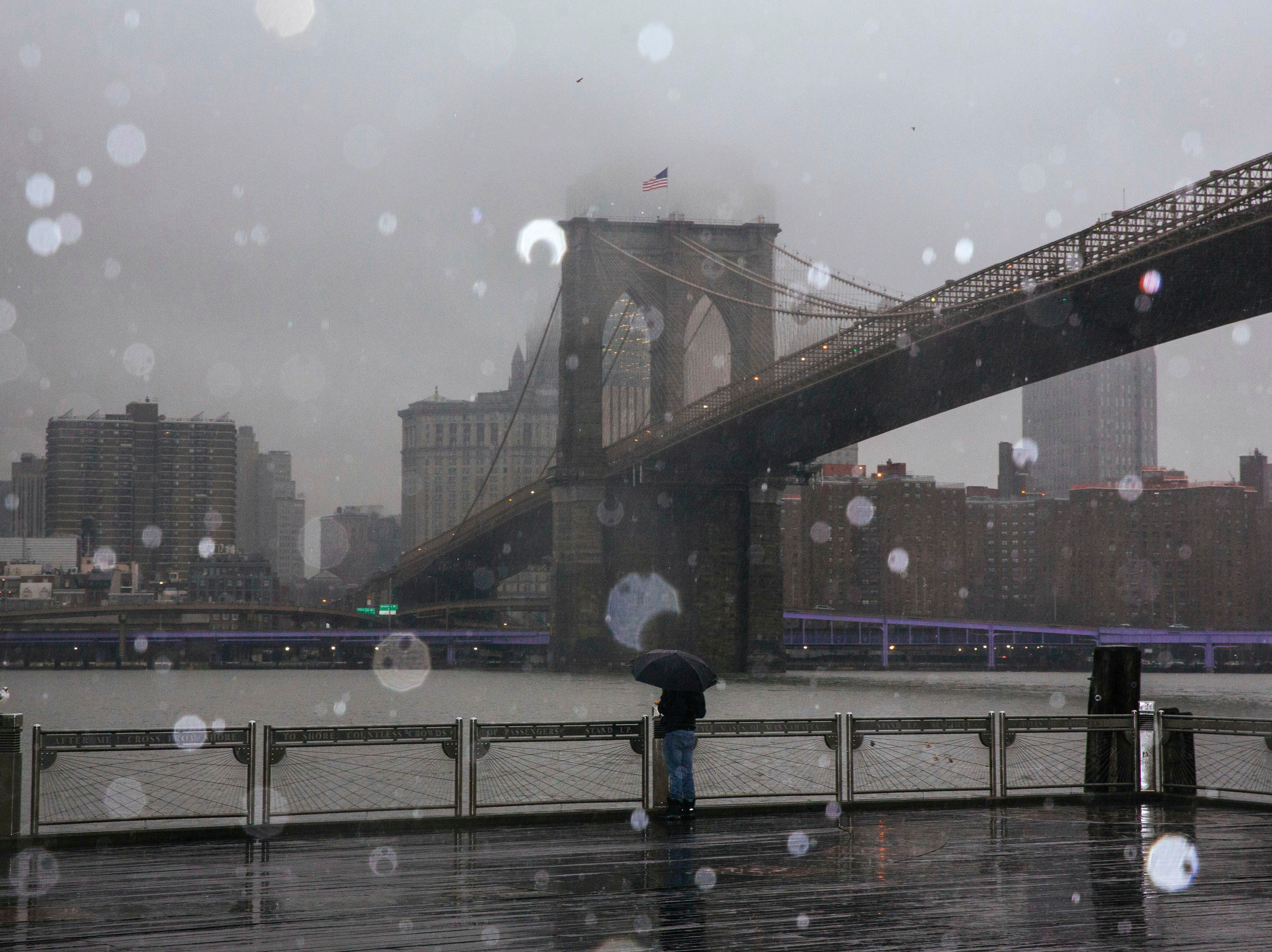 A man stands on the boardwalk at Brooklyn Bridge Park Sunday, Jan. 20, 2019, in New York. The National Weather Service said on Saturday that a dramatic drop in temperatures could turn the weekend's rainfall into ice before Monday. (AP Photo/Kevin Hagen). ORG XMIT: NYKH106
