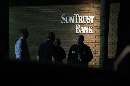Law enforcement officials investigate the scene where five people were killed at a SunTrust Bank branch on January 23, 2019 in Sebring, Florida.
