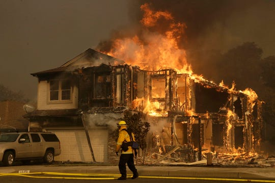 A firefighter walks near a flaming house in Santa Rosa, Calif., on Oct. 9, 2017.