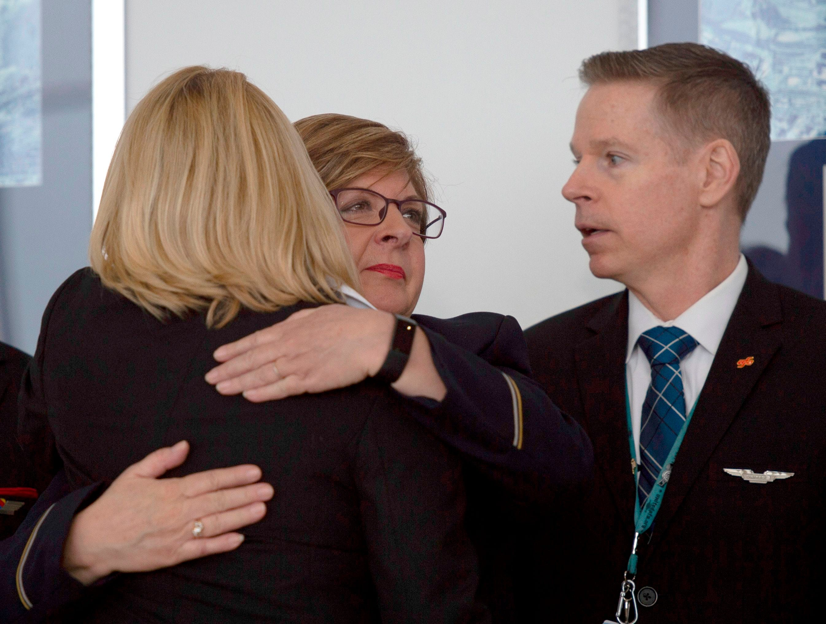 Airline employees hug before a press conference on aviation safety during the shutdown at Ronald Reagan Washington National Airport in Arlington, Va. on Jan.24, 2019.