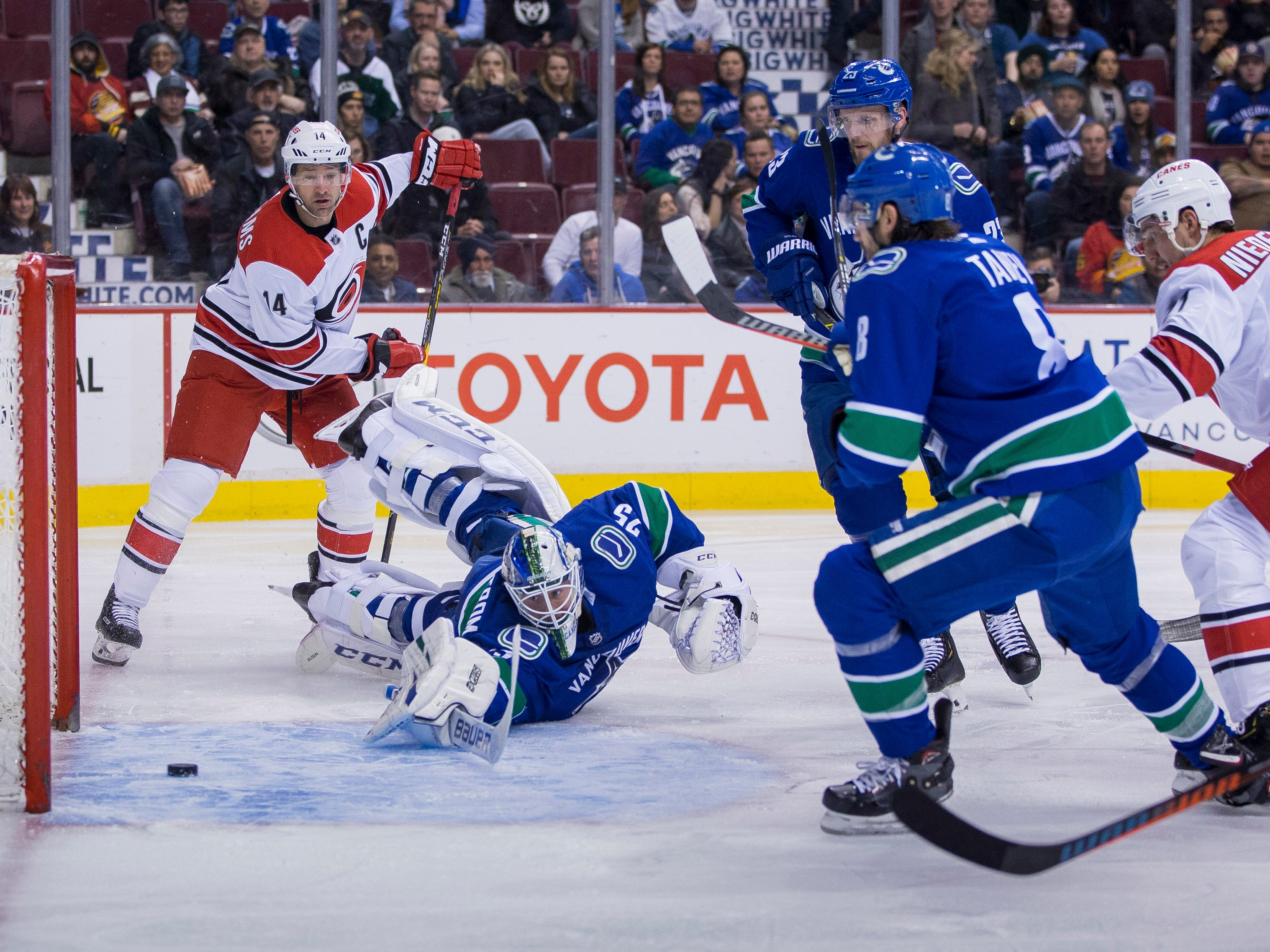 Jan. 23: Carolina Hurricanes forward Justin Williams (14) watches a shot from forward Nino Niederreiter (21) go past Vancouver Canucks goalie Jacob Markstrom in the second period at Rogers Arena. Carolina won the game, 5-2.