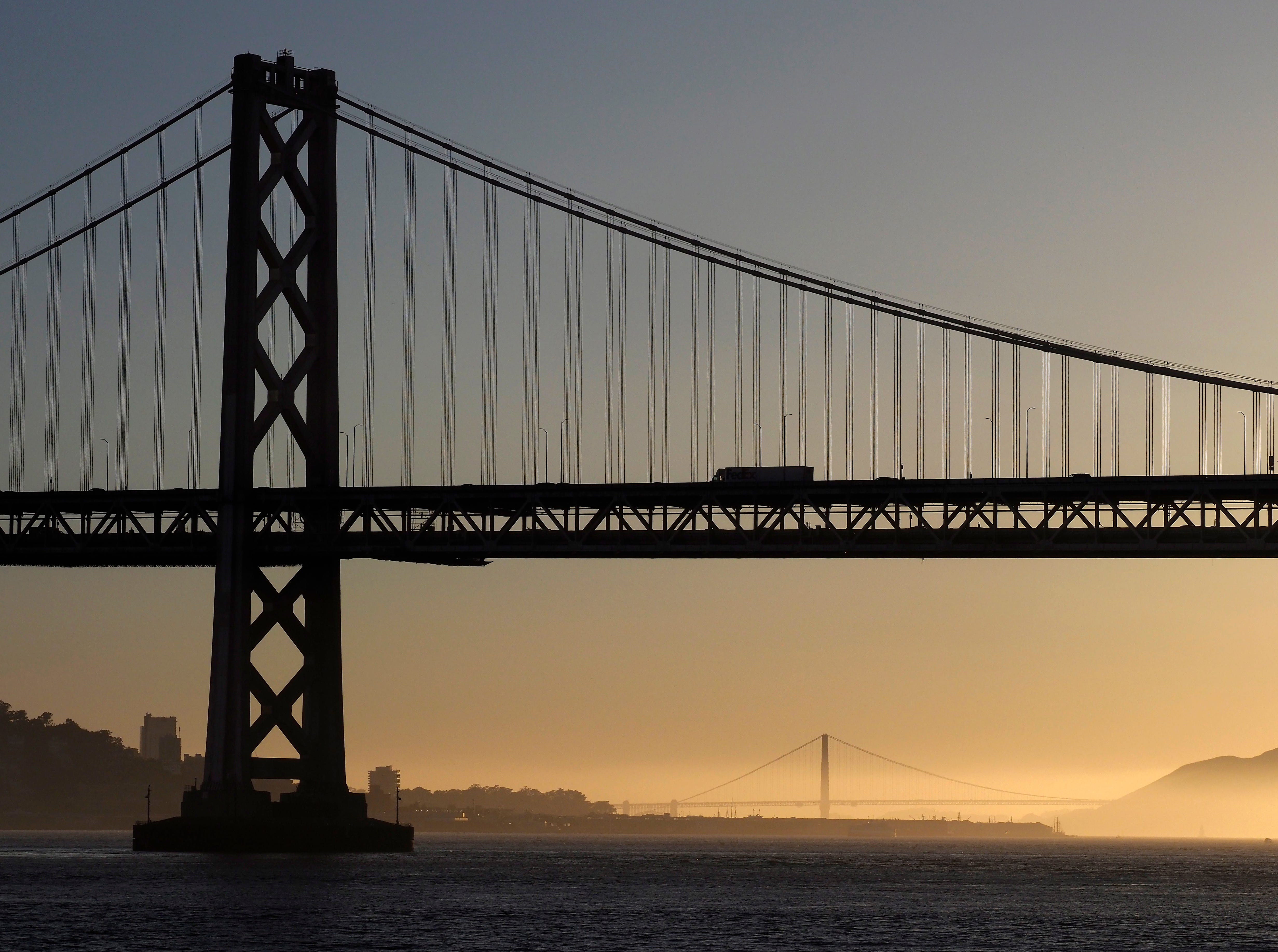 epa06729645 The San Francisco Bay Bridge in the foreground and the Golden Gate Bridge in the background at sunset as seen from the San Francisco Bay in San Francisco, California, USA, 11 May 2018.  EPA-EFE/JOHN G. MABANGLO ORG XMIT: JGM32