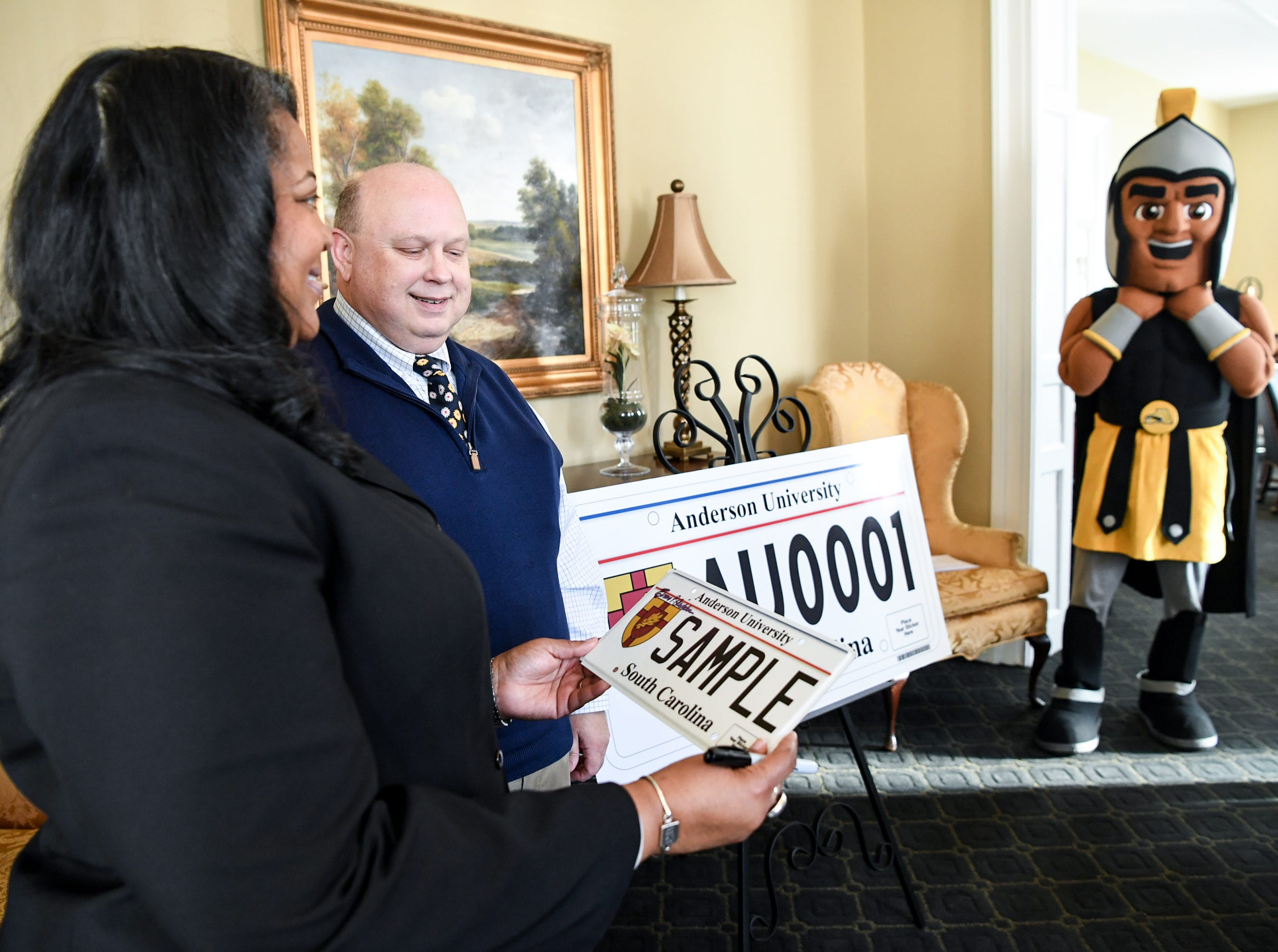 Hermena Perkins-Brown, left, plate office director of the South Carolina Department of Motor Vehicles, shows President Evans Whitaker of Anderson University and other officials a new personalized license plate during a press conference at the campus administration building in Anderson Friday morning. The University plate, along with Clemson University and the University of South Carolina, are the only college or university plates available to personalize, said Perkins-Brown. The Anderson University plates can be applied for starting Monday, January 28, 2019 in person, not online, for $100 and an added fee if personalizing.