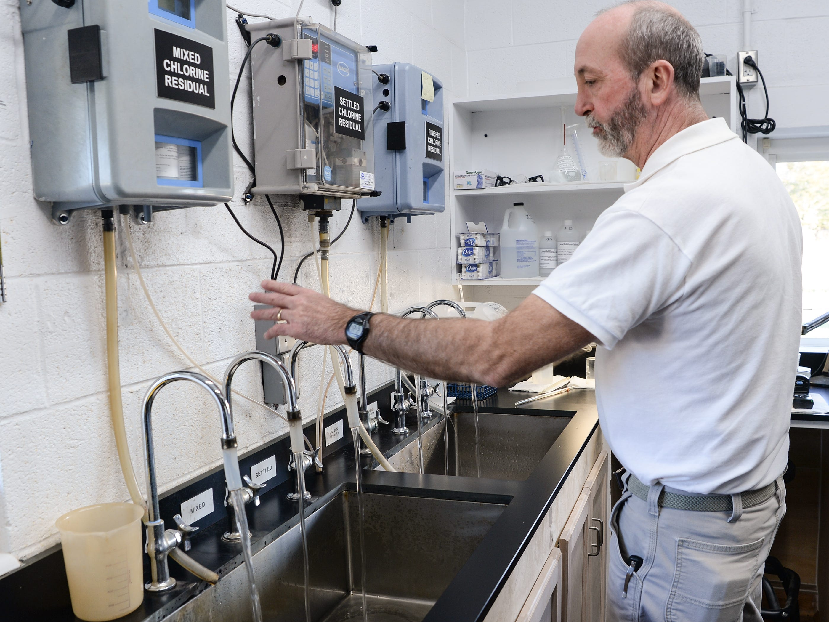 Mitch Ellenburg, general manager at the Belton Honea Path Water Authority in Honea Path looks at quality of water from each filtration step flowing through a faucet on Friday.
