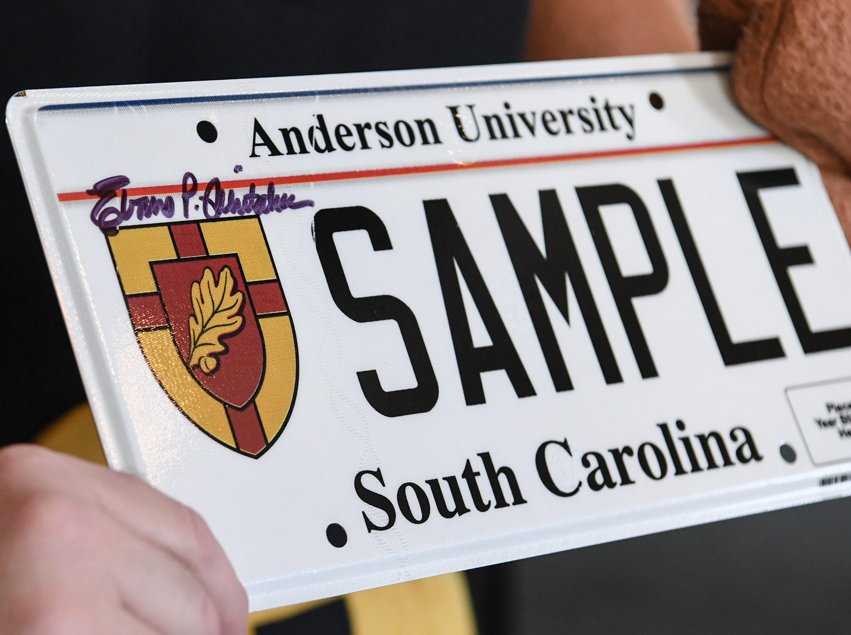 President Evans Whitaker of Anderson University autographs a new school personalized license plate for a display, during a press conference at the campus administration building in Anderson Friday morning. The University plate, along with Clemson University and the University of South Carolina, are the only college or university plates available to personalize, said Perkins-Brown. The Anderson University plates can be applied for starting Monday, January 28, 2019 in person, not online, for $100 and an added fee if personalizing.