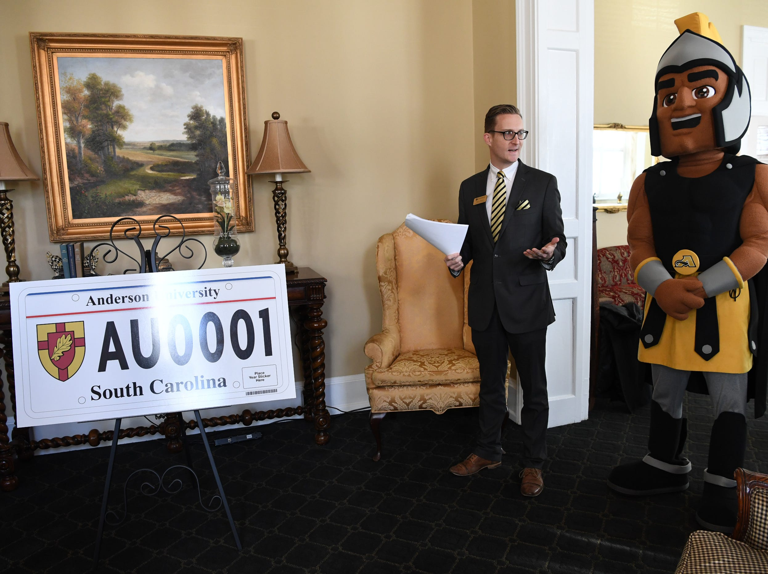 Andrew Beckner, left, of Anderson University media relations, and Troy the Trojans mascot gather to announce a new personalized license plate during a press conference at the campus administration building in Anderson Friday morning. The University plate, along with Clemson University and the University of South Carolina, are the only college or university plates available to personalize, said Perkins-Brown. The Anderson University plates can be applied for starting Monday, January 28, 2019 in person, not online, for $100 and an added fee if personalizing.