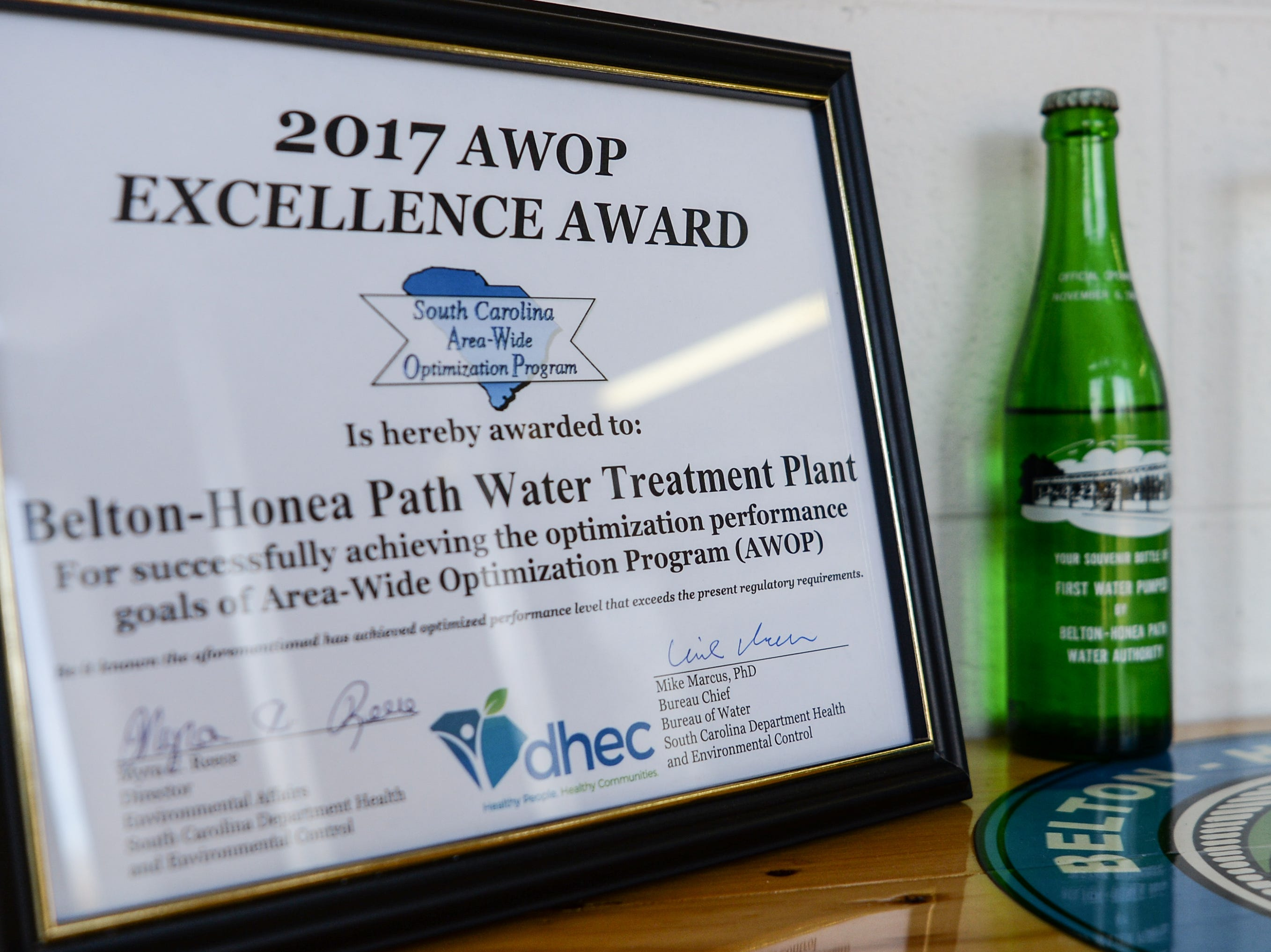 An award from 2017 for excellence next to a bottle of water saved from 1968, when the Belton Honea Path Water Authority plant opened in Honea Path.