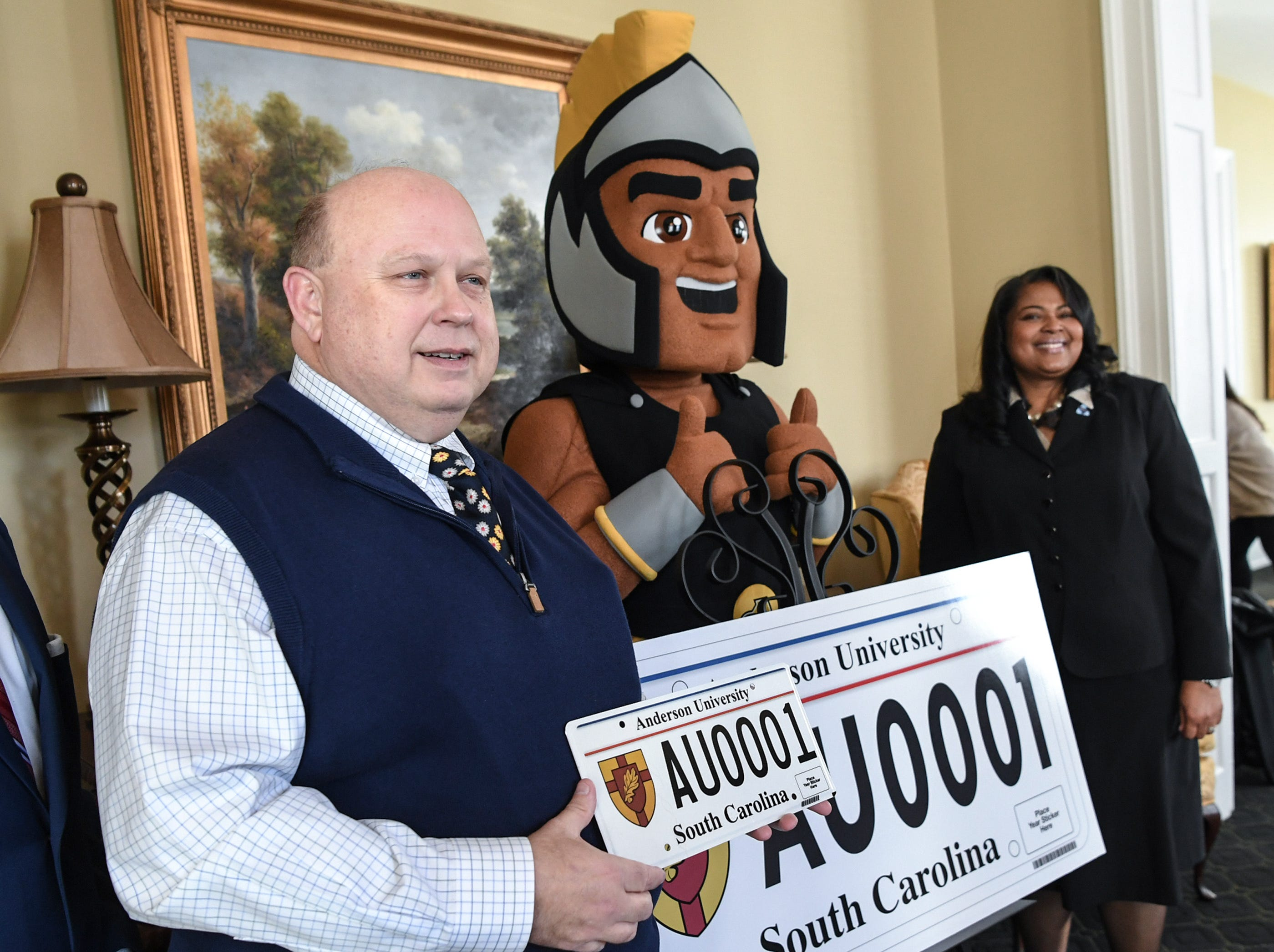 President Evans Whitaker, left, Troy the Trojans mascot, of Anderson University and Hermena Perkins-Brown, right, plate office director of the South Carolina Department of Motor Vehicles, show other officials a new personalized license plate during a press conference at the campus administration building in Anderson Friday morning. The University plate, along with Clemson University and the University of South Carolina, are the only college or university plates available to personalize, said Perkins-Brown. The Anderson University plates can be applied for starting Monday, January 28, 2019 in person, not online, for $100 and an added fee if personalizing.