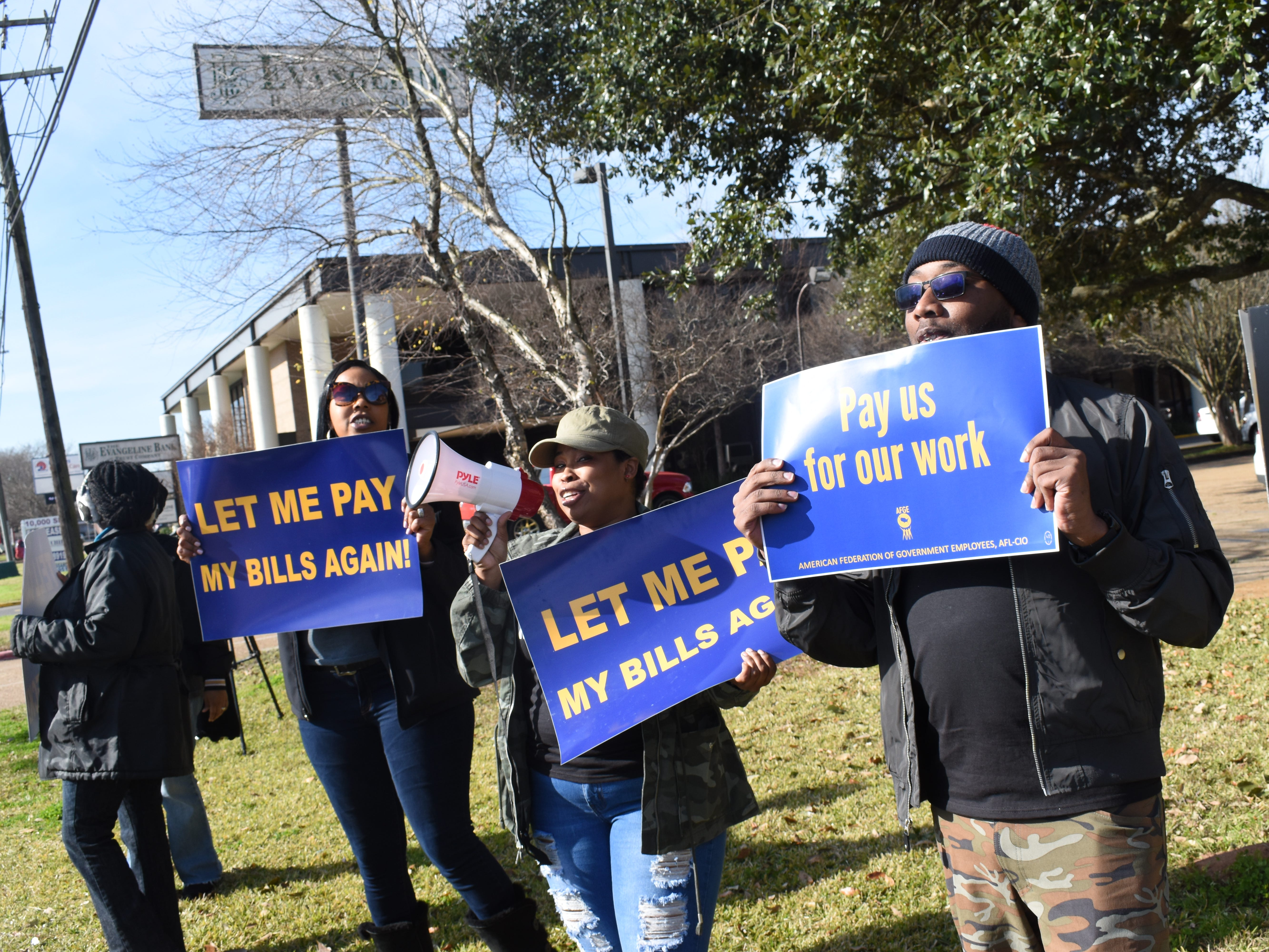 Nekesha Harvey (left), Victoria Battles and Michael Anderson, who work at the Federal Correctional Complex in Pollock and are members of the American Federation of Government Employees Local 1034, rally with other AFGE members outside U.S. Sen.Bill Cassidy's office located on Jackson Street Extension on Friday, Jan. 25, 2019. 