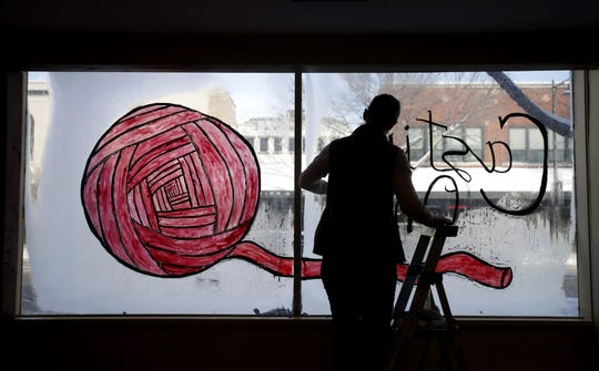 Sam Rabideau, co-owner of the new yarn shop Casting On, scrapes a temporary sign off the front window before opening day.