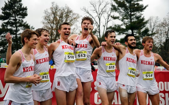 Members of the Neenah boys cross country team celebrate after winning the WIAA Division 1 state cross country championship at Ridges Golf Course in Wisconsin Rapids on Oct. 27.