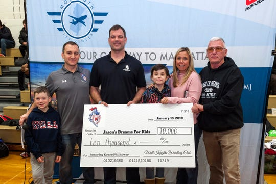 Dennis McGinnis, far right, accepts a $10,000 donation for Jason's Dreams For Kids at the Wall Takedown Pediatric Cancer Tournament. Pictured with him are (left to right) Nolan Parnell, Michael Parnell, Rob Philhower, Grace Philhower, and Jackie Philhower.
