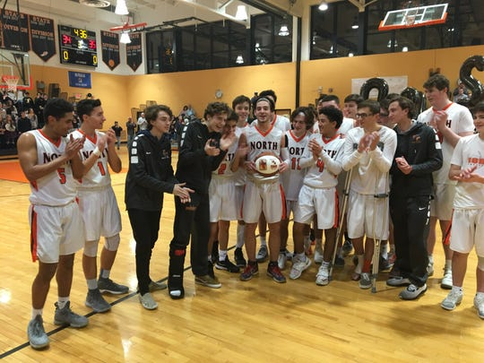 Middletown North's Rob Higgins (center) gets congratulated by his teammates after he scored his 2,000 career points in a 66-63 loss to Neptune on Jan. 24, 2019 at Middletown North High School.