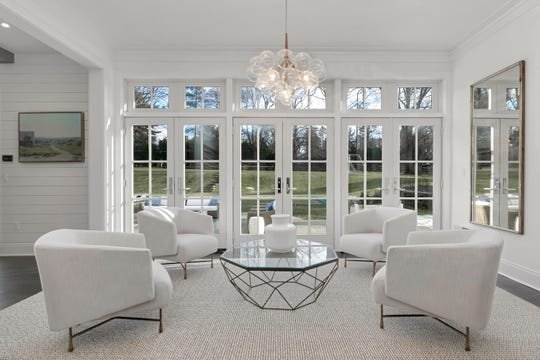 The Living room features decorative molding, a set of French Doors and amazing chandelier.