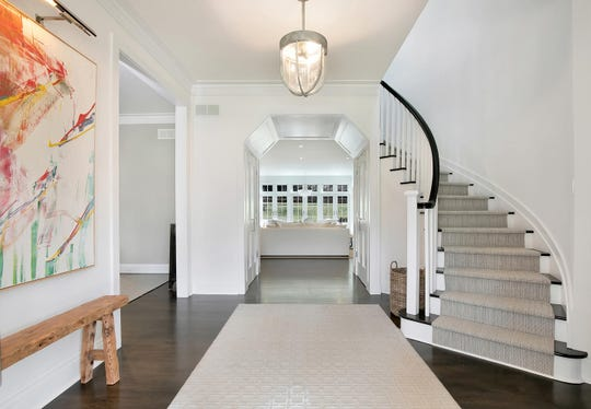 The Foyer offers a spiral staircase with beautiful crown molding and spectacular farmhouse.