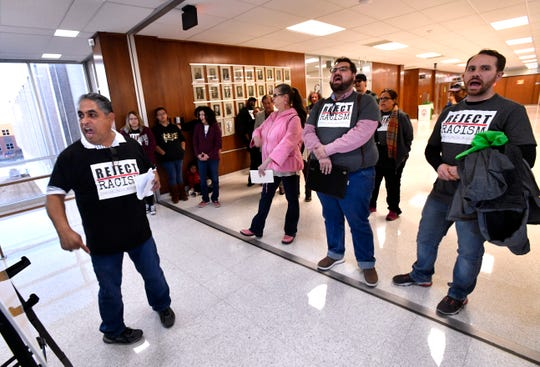 "AISD board member Samuel Garcia (left) and others chant ""Shame!"" after the Abilene City Council voted Thursday not to change the agenda to allow for public comment before voting on the censure of member Kyle McAlister. Garcia and others left the chambers to stand in the hallway outside to voice their displeasure."