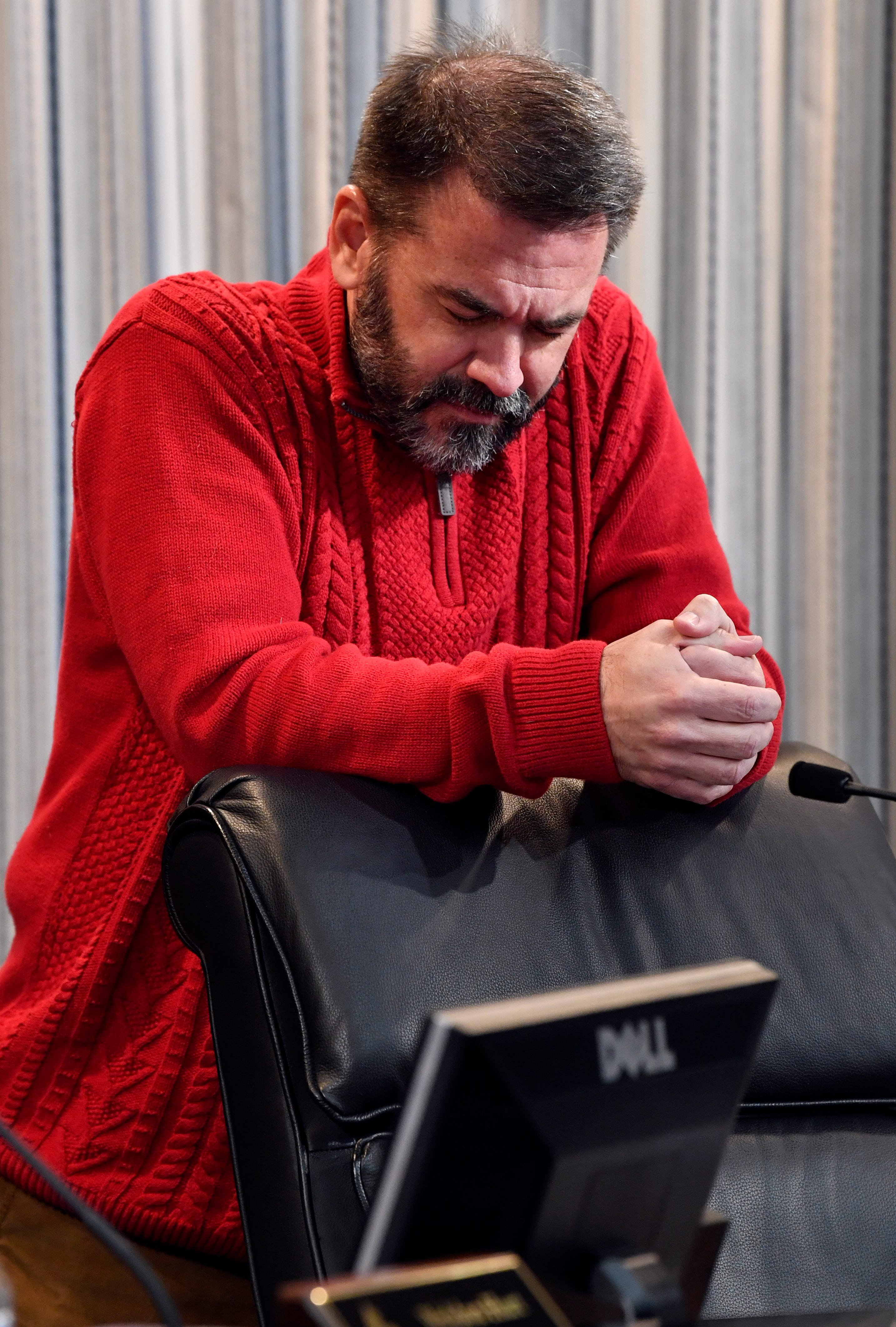 Abilene City Councilman Kyle McAlister bows his head in prayer during the invocation by fellow council member Donna Albus at the start of Thursday's meeting at City Hall Jan. 24, 2019. A measure to censure McAlister for social media posts some have found racially insensitive did not pass.