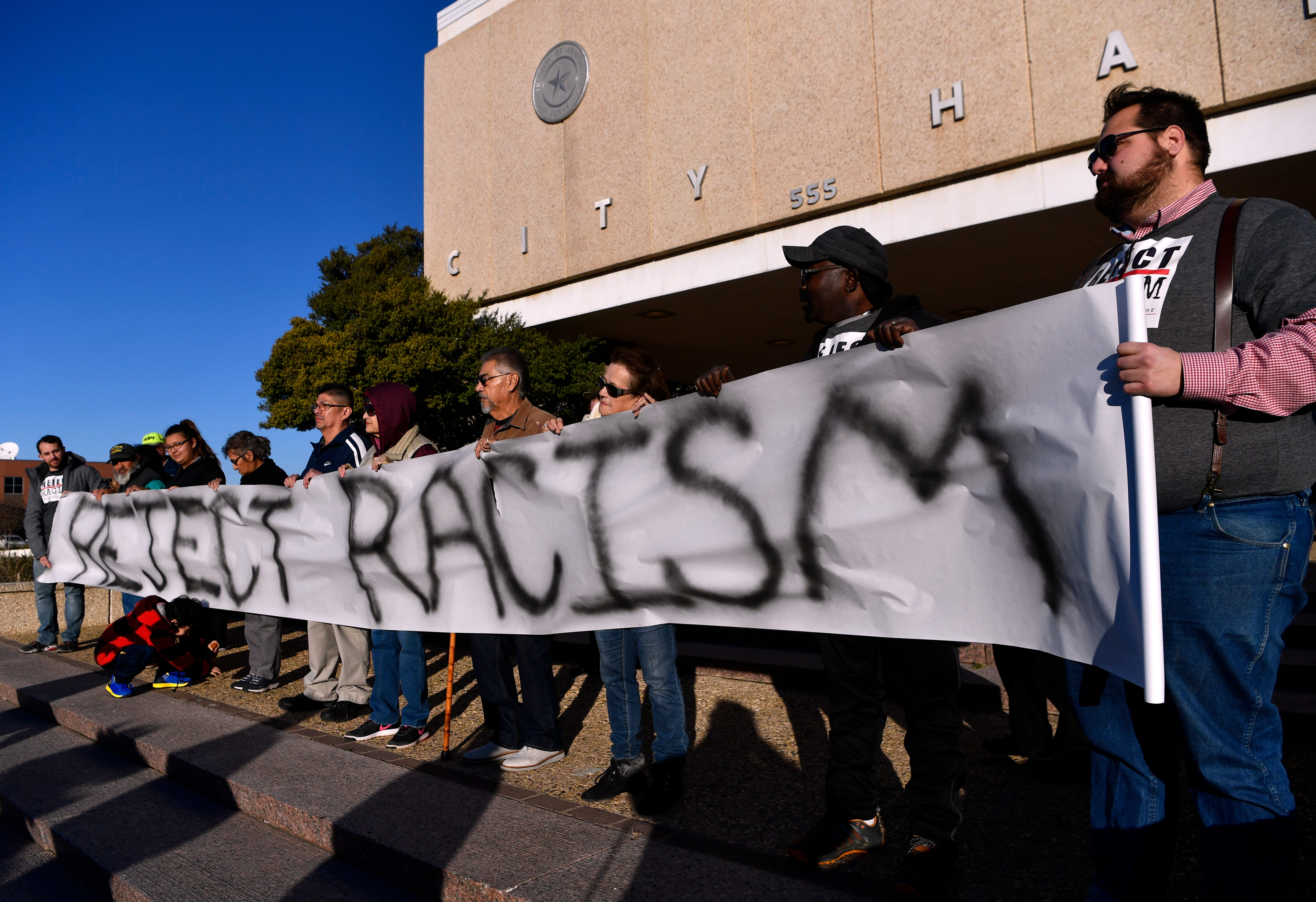 Protesters hold a paper banner in front of Abilene City Hall Thursday Jan. 24, 2019 before the City Council meeting. The council was scheduled to vote on a censure of member Kyle McAlister whose social media posts have been labeled as racist by community members.